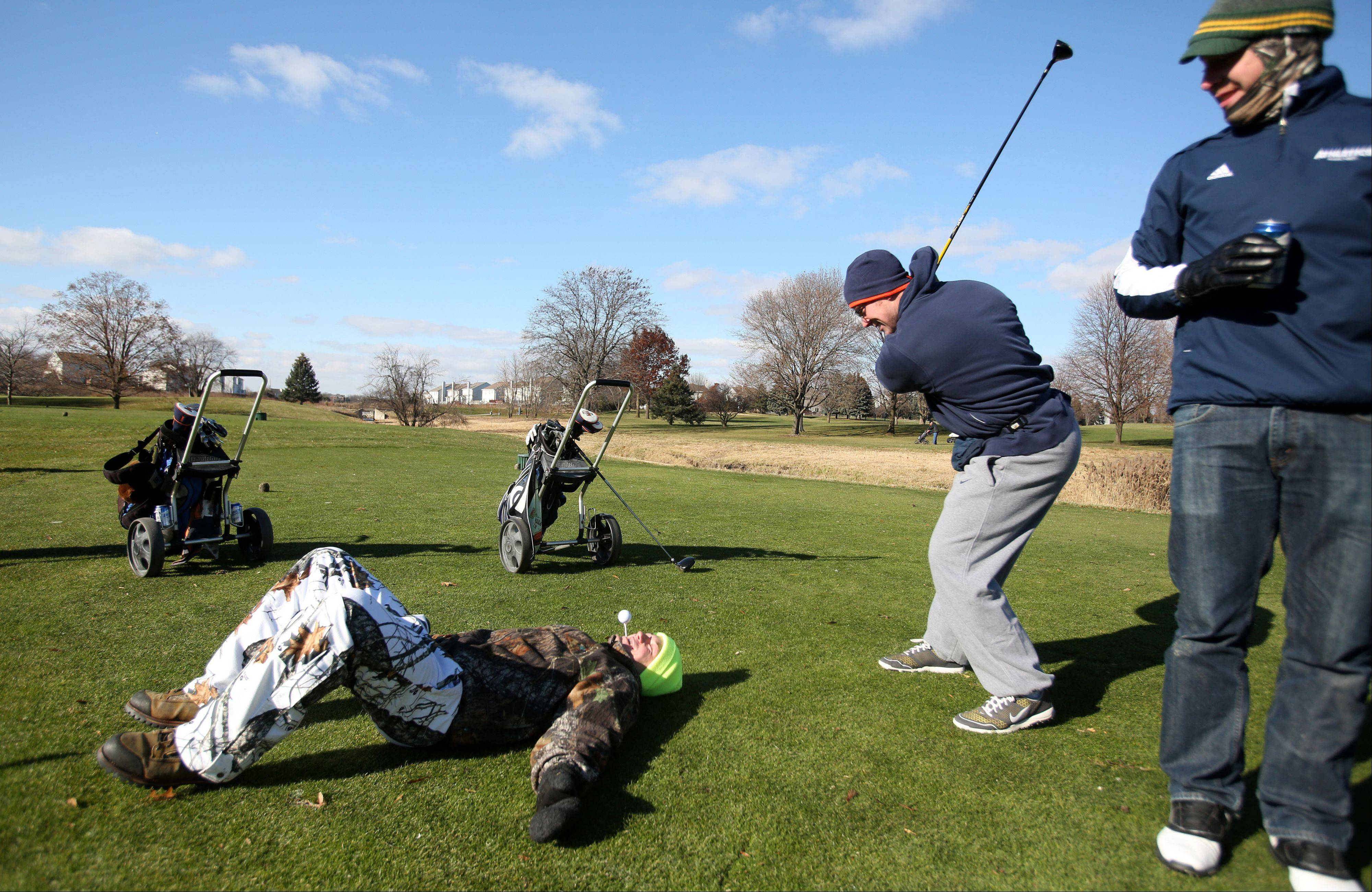 Derek Weber of Joliet lies on the ground as the human tee during the Naperville Park District's Turkey Shoot golf tournament Saturday at Springbrook Golf Course in Naperville. Zach Pedersen of Joliet practices his backswing while Dan Hamburger of Naperville watches.