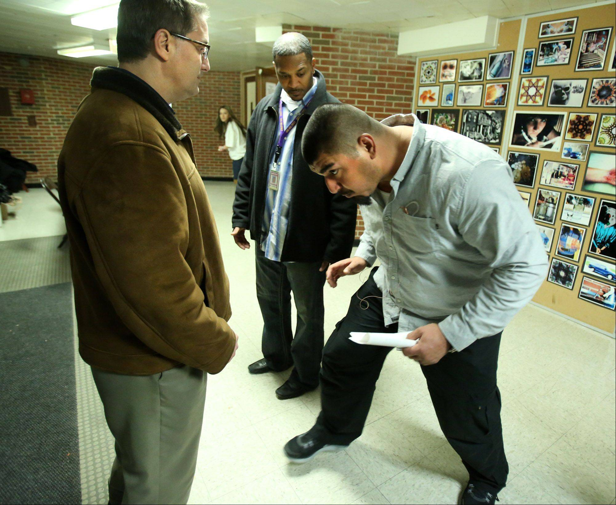 Bears center Roberto Garza, right, reviews offensive plays with Waukegan High School varsity linebacker coach Chris Lacivita, left, and head coach Nick Browder in the school auditorium lobby Friday before Garza took the stage for fundraiser.