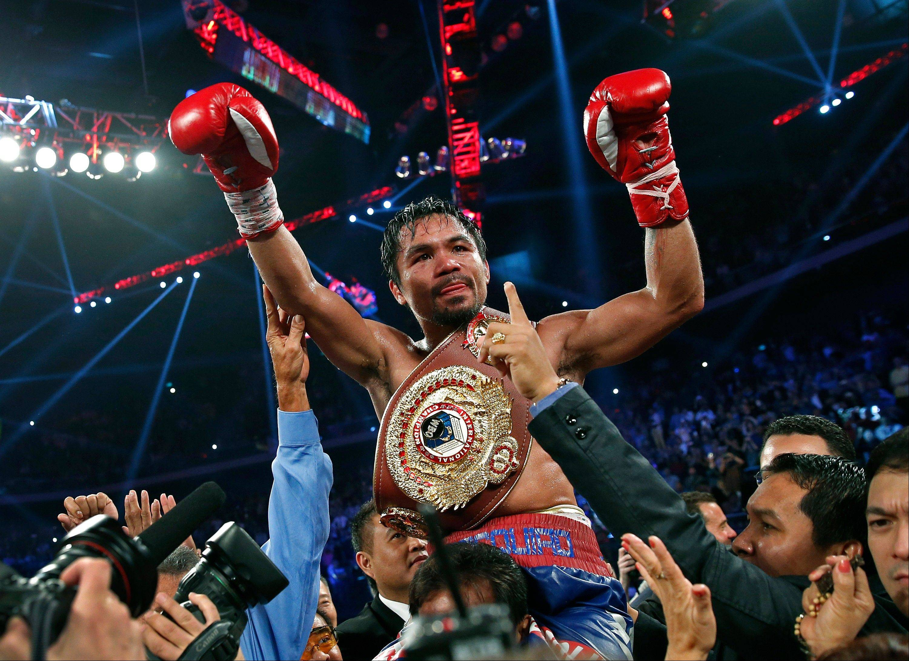 Manny Pacquiao wears the champion's belt after defeating Brandon Rios in their WBO international welterweight title fight on Sunday in Macau.