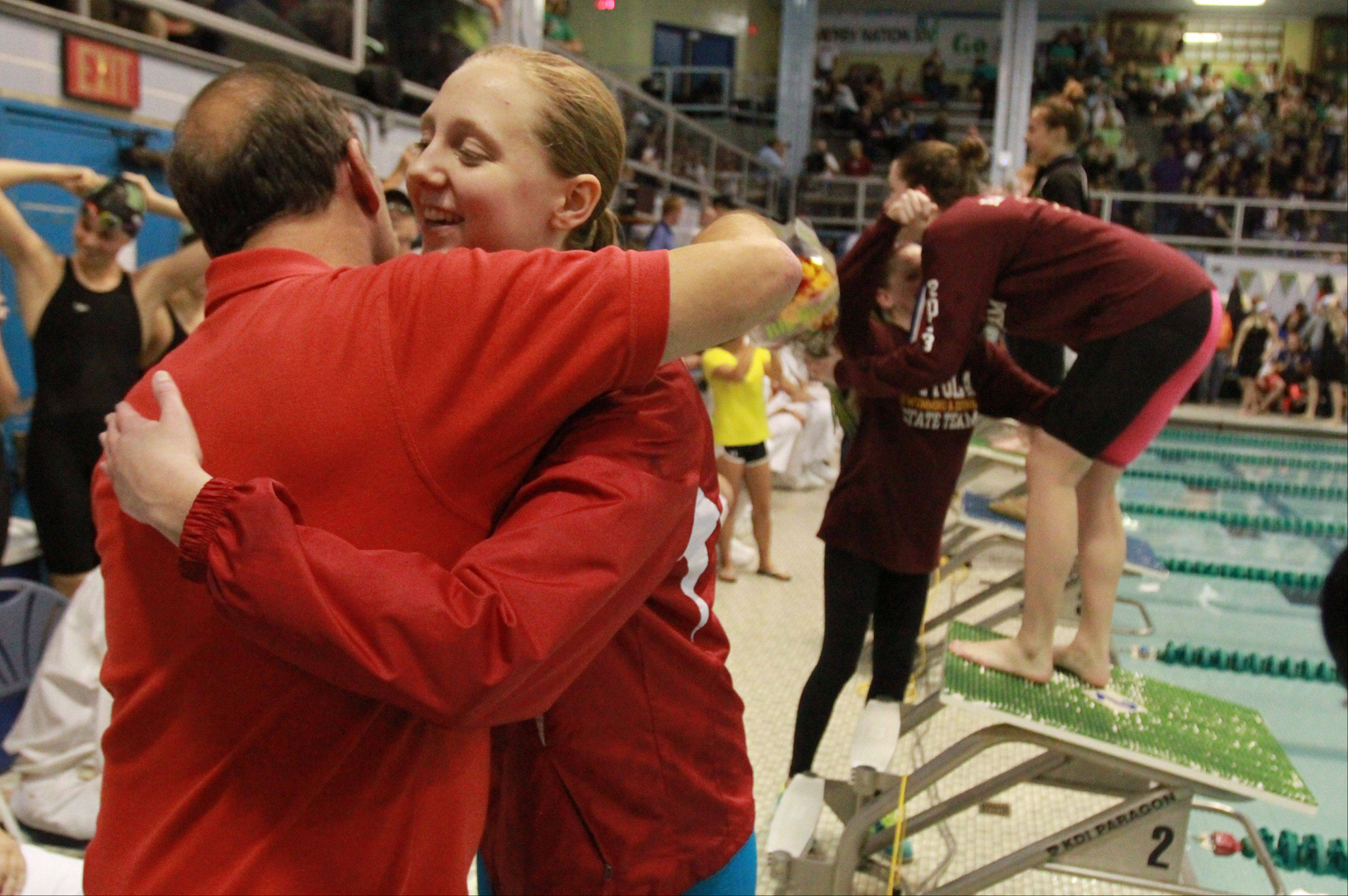 Barrington's Kristen Jacobsen gets a hug from coach Jim Bart while getting her award for winning the 500-yard freestyle in Saturday's state finals at New Trier.