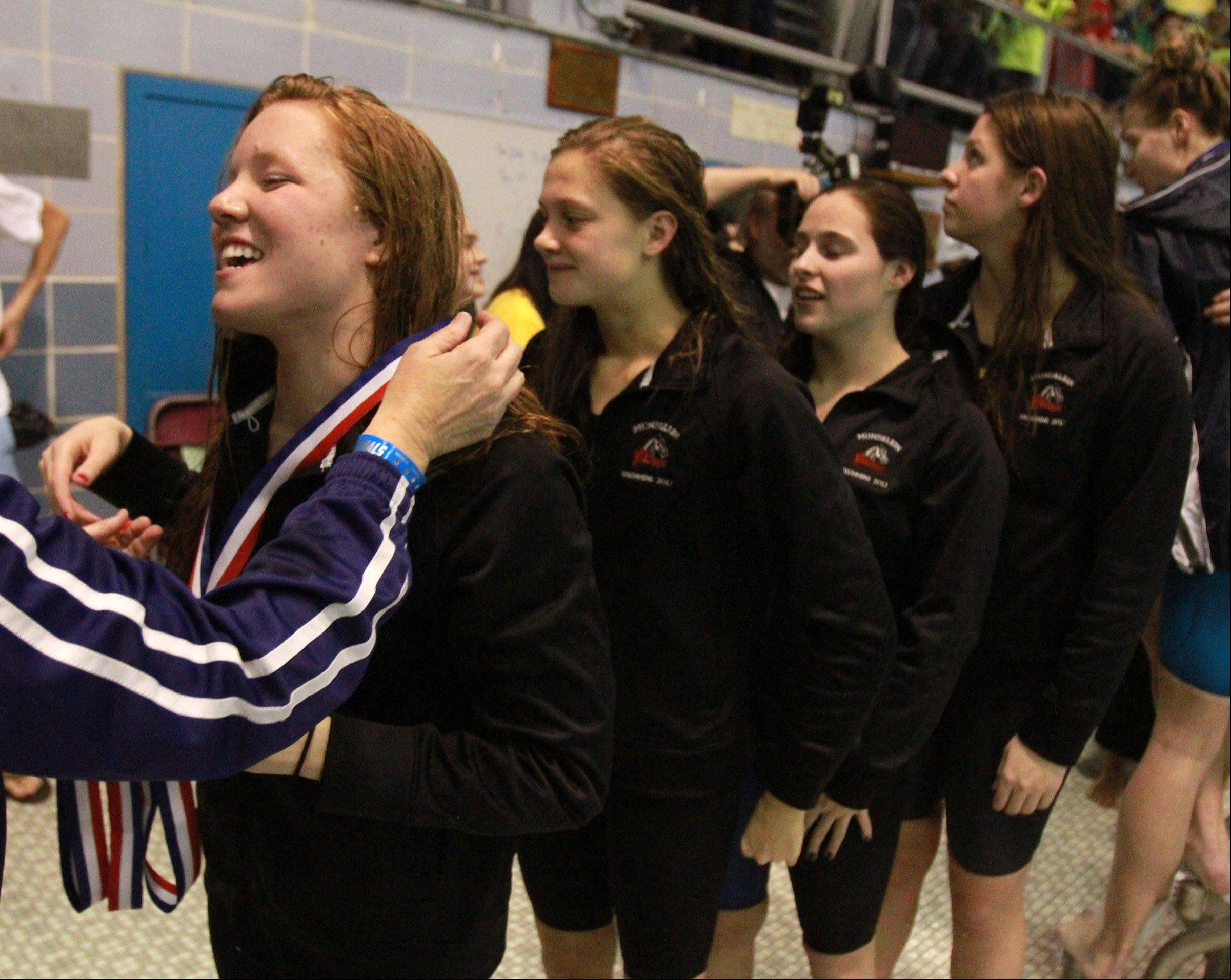 Mundelein's Erin Falconer, Karrie Kozokar, Rachel Robb and Jennifer Kordik receives their medals for fourth-place finish in the 400-yard freestyle relay at the girls swimming state finals on Saturday at New Trier.