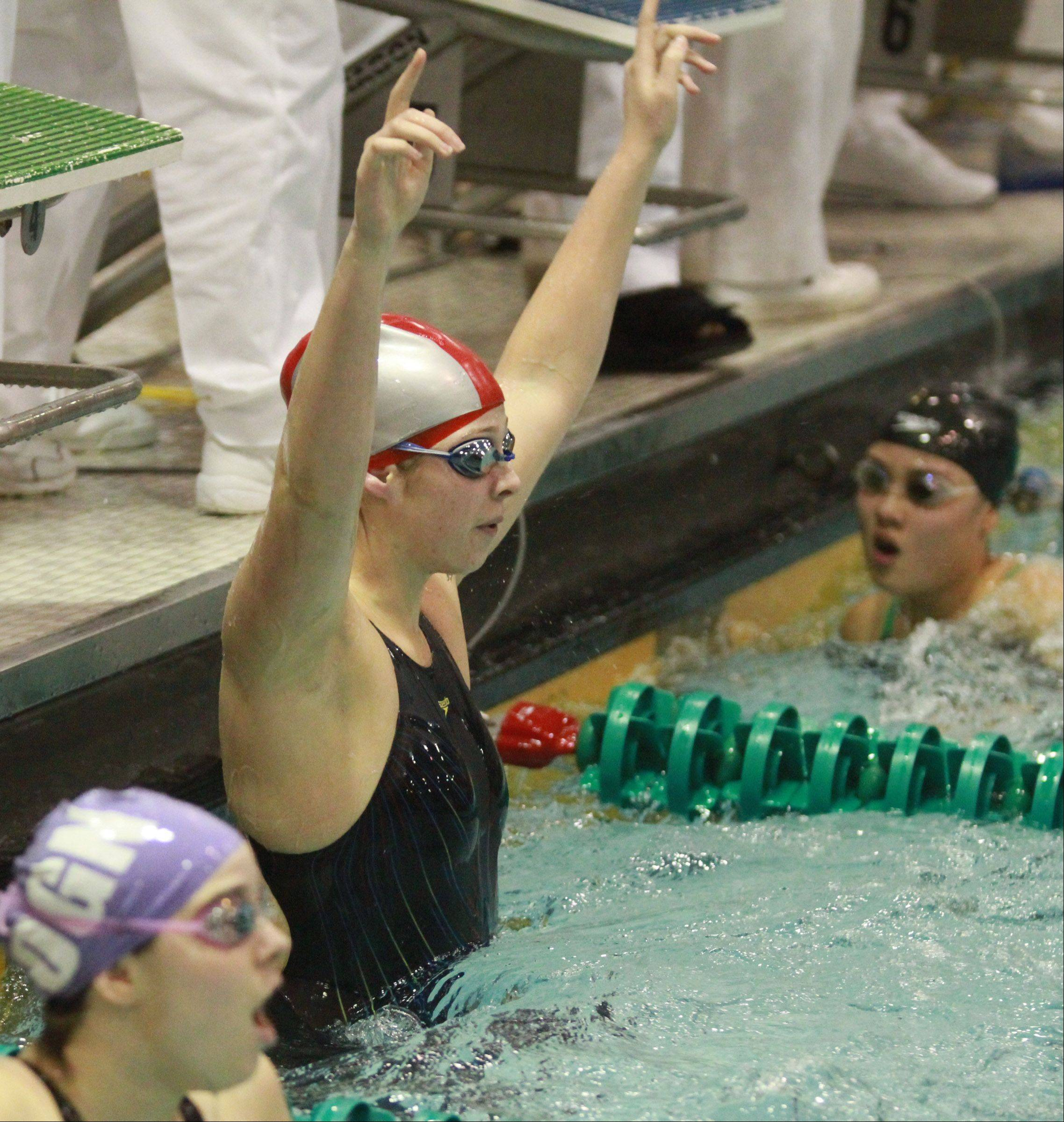 Mundelein's Karrie Kozokar celebrates winning the 200 yard freestyle relay after swimming the final leg in the event at the girls state swimming finals on Saturday in Winnetka.