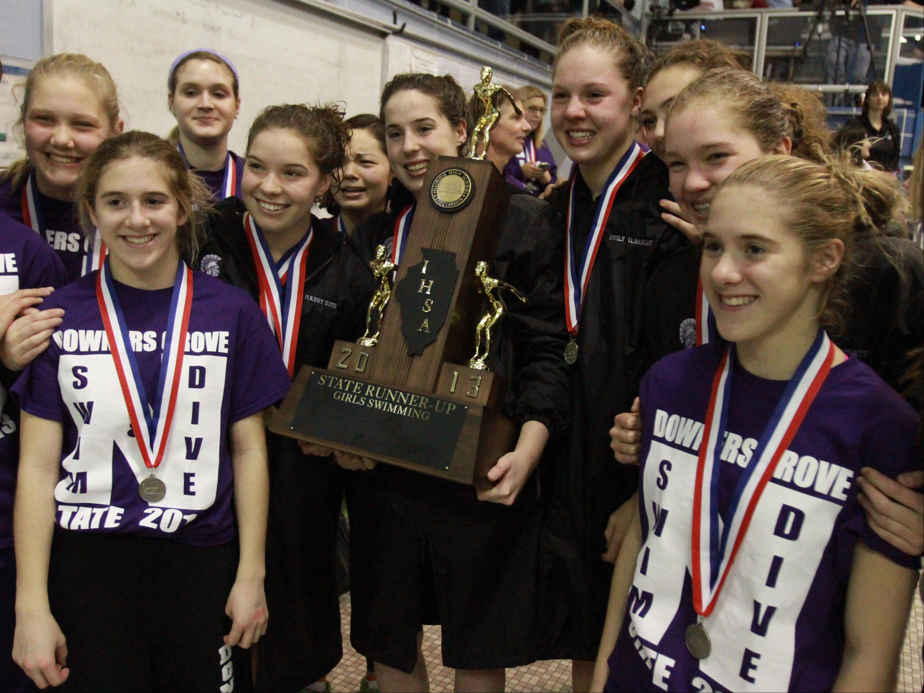 Downers Grove North's Gabby Sims holds up the runner up team trophy as the rest of the girls swim and dive team pose with the 2nd place trophy at state swimming finals on Saturday in Winnetka.