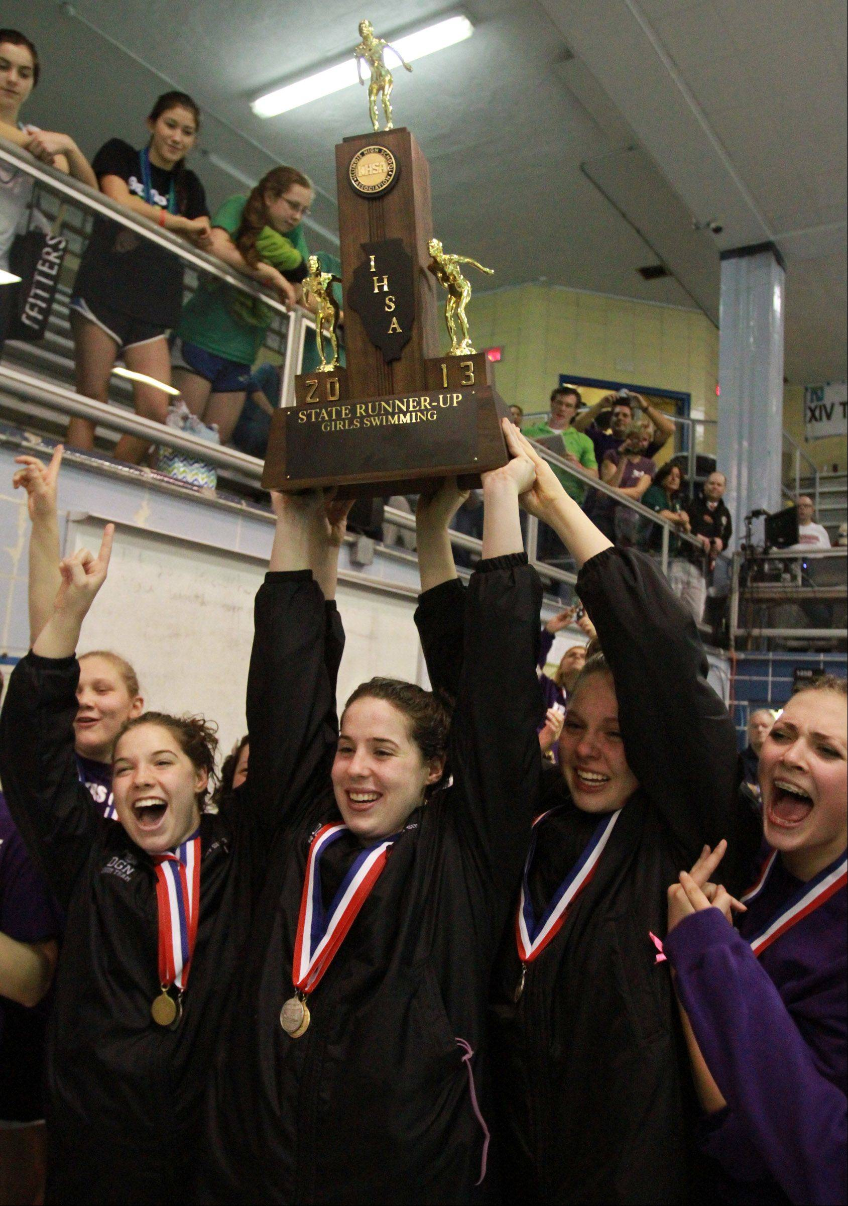 Downers Grove North's Gabby Sims holds up the runner up team trophy as the rest of the girls swim and dive team celebrates placing 2nd at state swimming finals on Saturday in Winnetka.