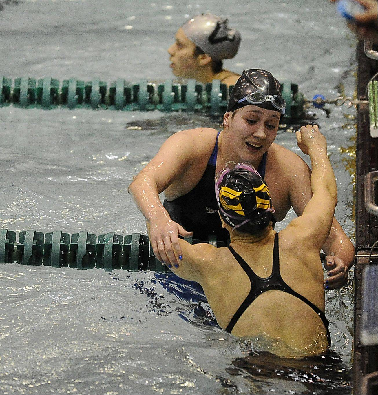 Monica Guyett of St. Charles North hugs Kira Webster of Normal University High after the 500-yd. freestyle at the girls state finals prelims at New Trier High School on Friday.