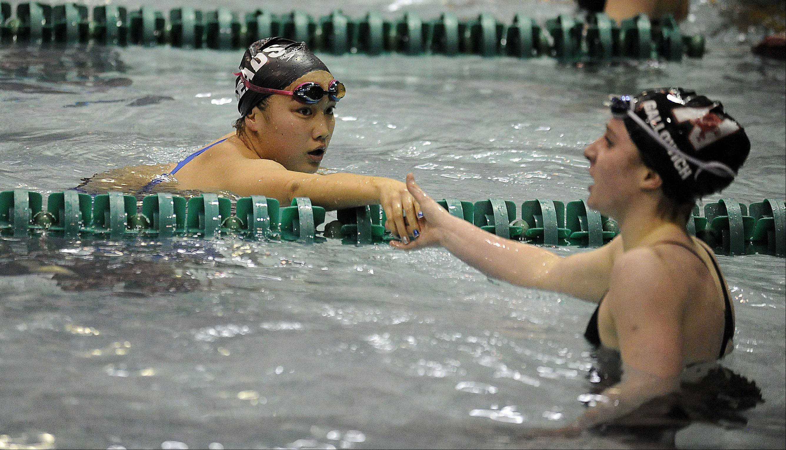 Annie Gosselin of Rosary, left, shakes hands with Kamryn Gallowich of Naperville Central after the 200-yd. individual medley.