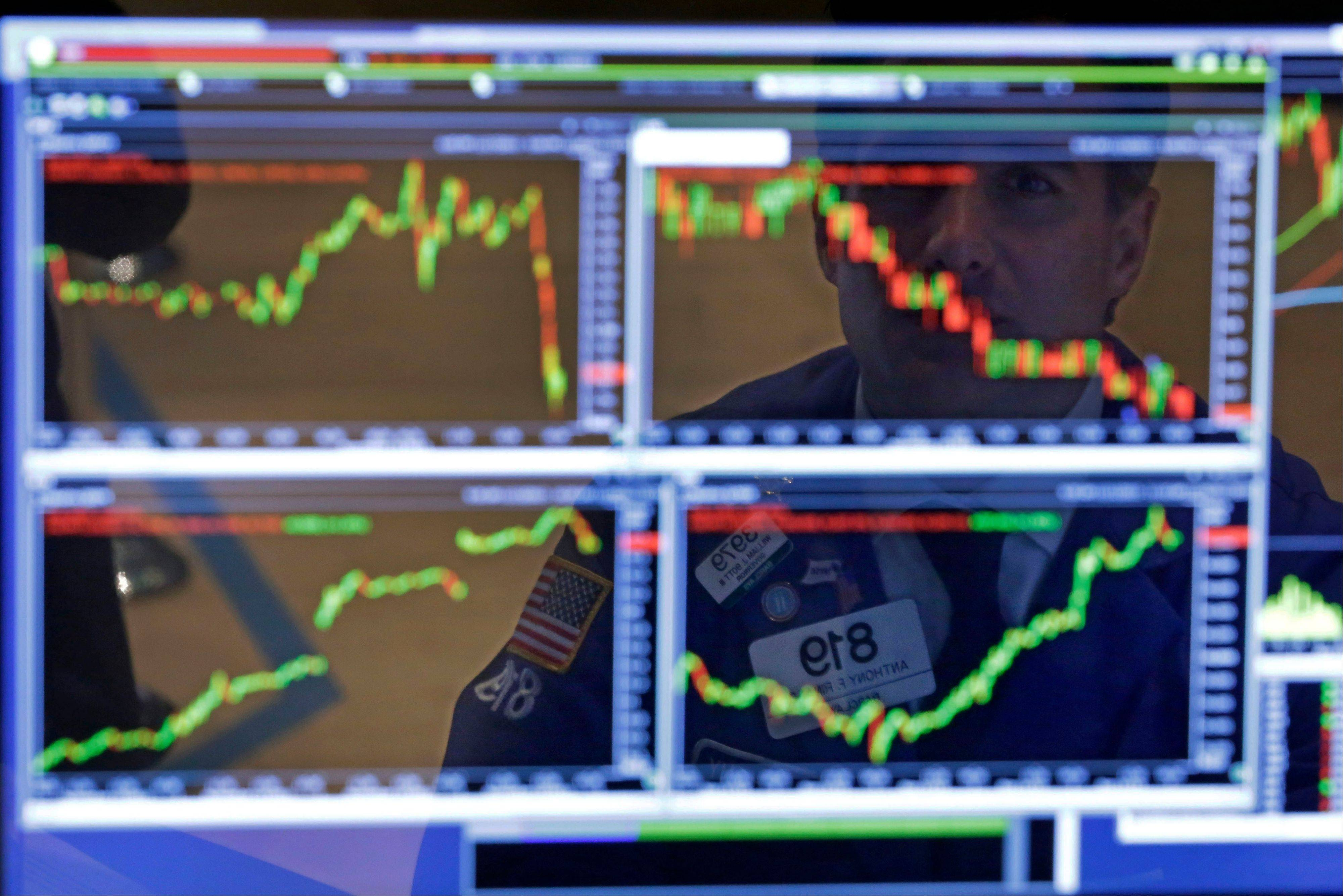 Specialist Anthony Rinaldi is reflected in one of his screens at his post on the floor of the New York Stock Exchange. The Dow Jones industrial average has surged 900 points since early October and crossed the 16,000-point threshold Monday.