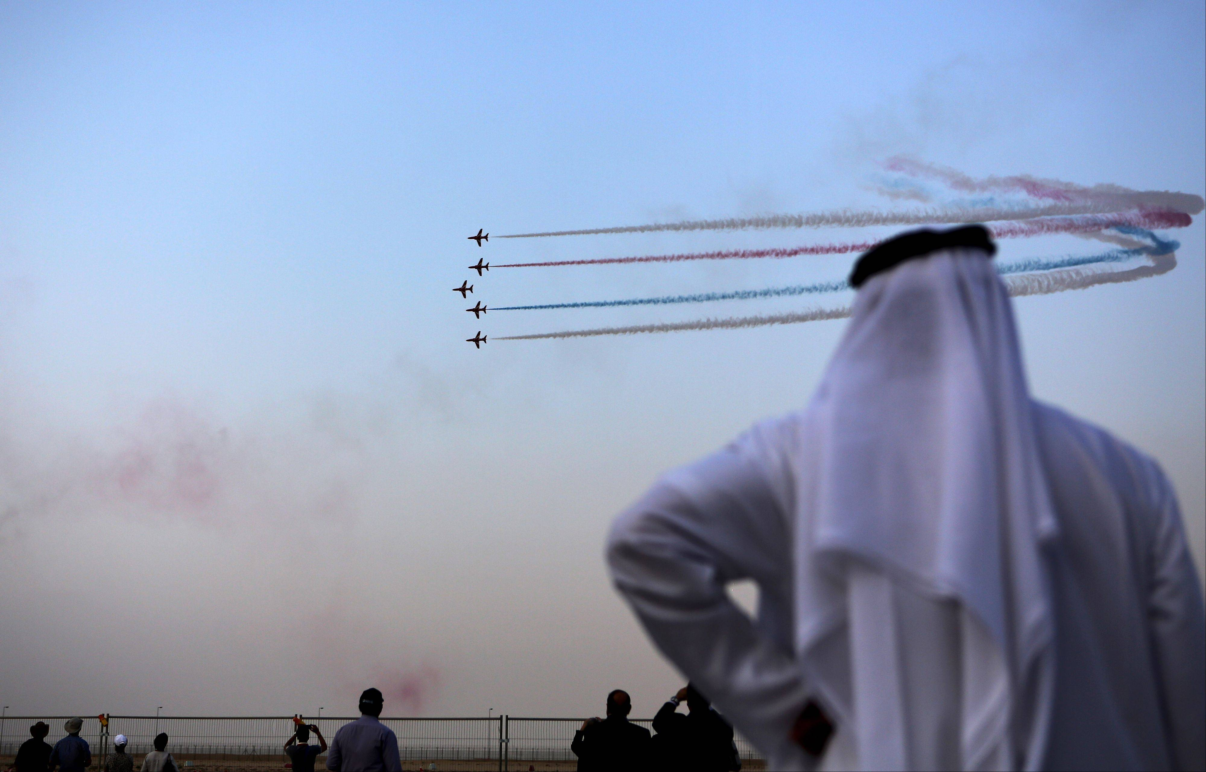 An Emirati visitor watches the Al Fursan, the aerobatics demonstration team of the UAE Air Force, Monday during the Dubai Airshow in Dubai, United Arab Emirates.