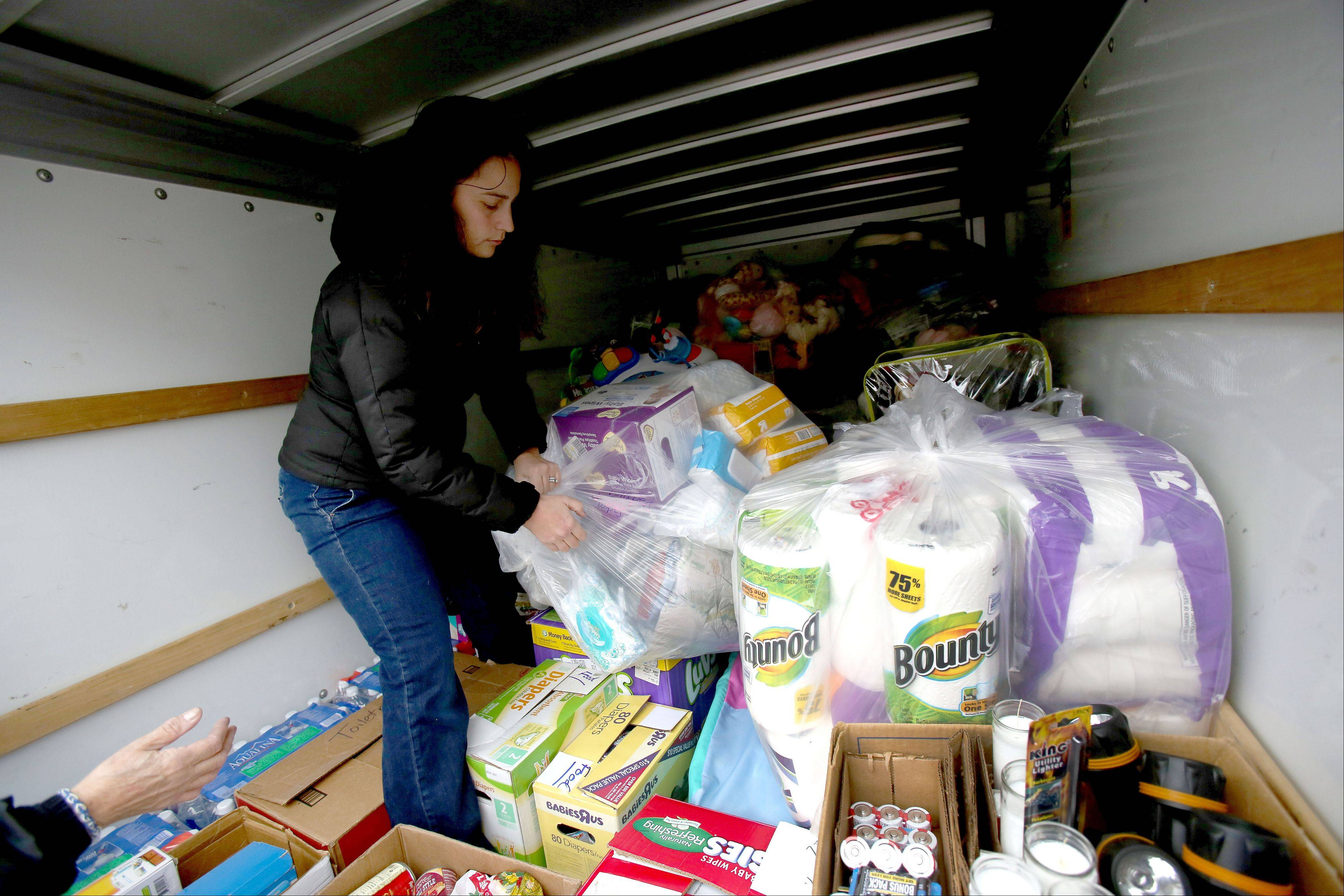 Bev Horne/bhorne@dailyherald.com Jennifer Guevara loads up a U-Haul on Thursday in Wheaton of donated items to take to the victims of the tornado in Coal City. She gathered donations after she posted on Wheaton, Illinois Parents Facebook page.