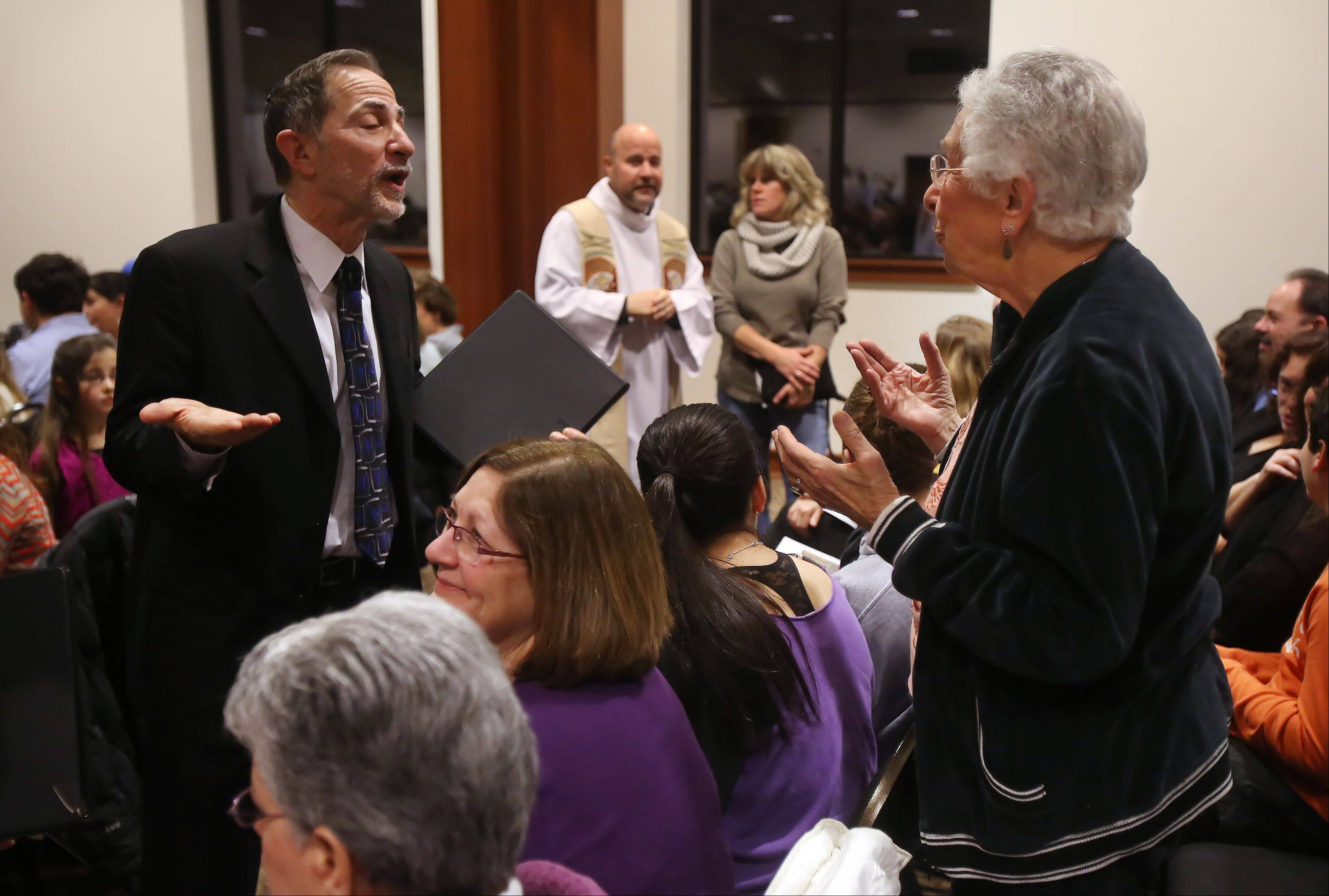 Congregation Beth Judea Cantor Roger Weisberg, left, talks with Paulette Kallow before the Interfaith Thanksgiving Celebration on Sunday night at Temple Chai in Buffalo Grove. Eight congregations of the Northwest Suburban Interfaith Council held a united service for a congregation of more than 800. In the background is Rev. Dan Whiteside of Saint Mary Catholic Church.