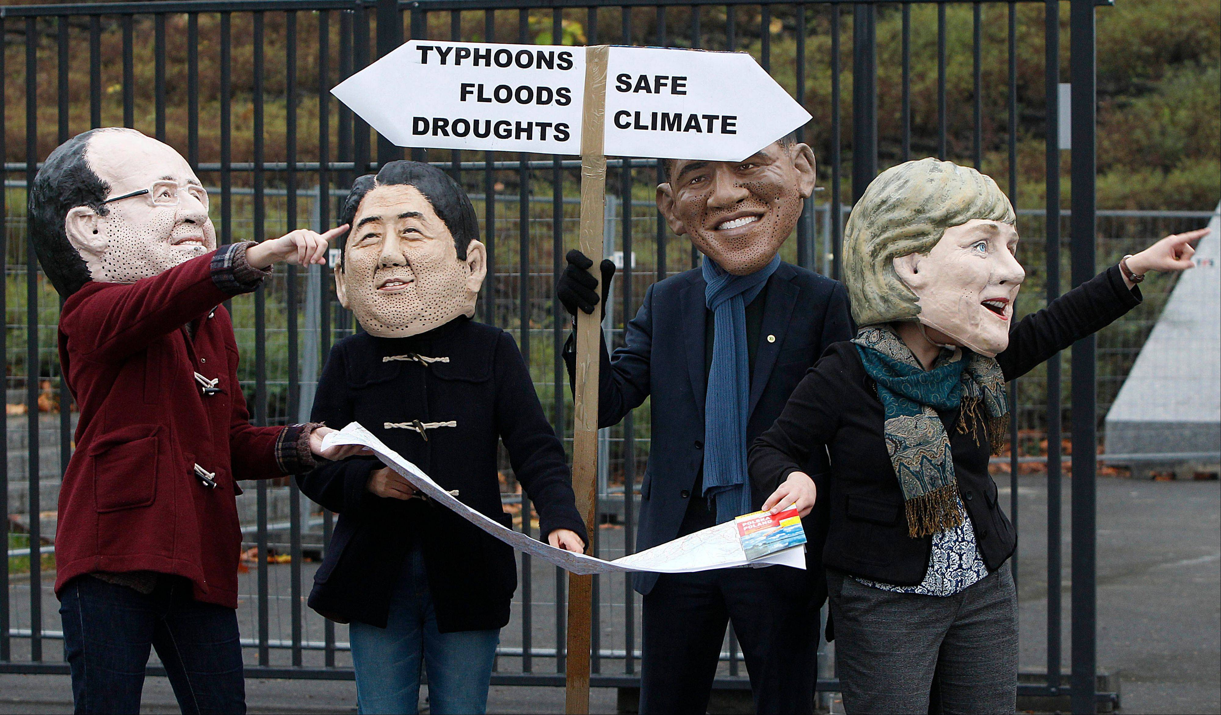 Climate activists protest acting in the role of world leaders who search for a way, in front of the U.N. climate change conference in Warsaw, Poland, Friday. They act, from left to right, as French President Francois Hollande, Japan's Prime Minister Shinzo Abe, U.S. President Barack Obama and German Chancellor Angela Merkel.