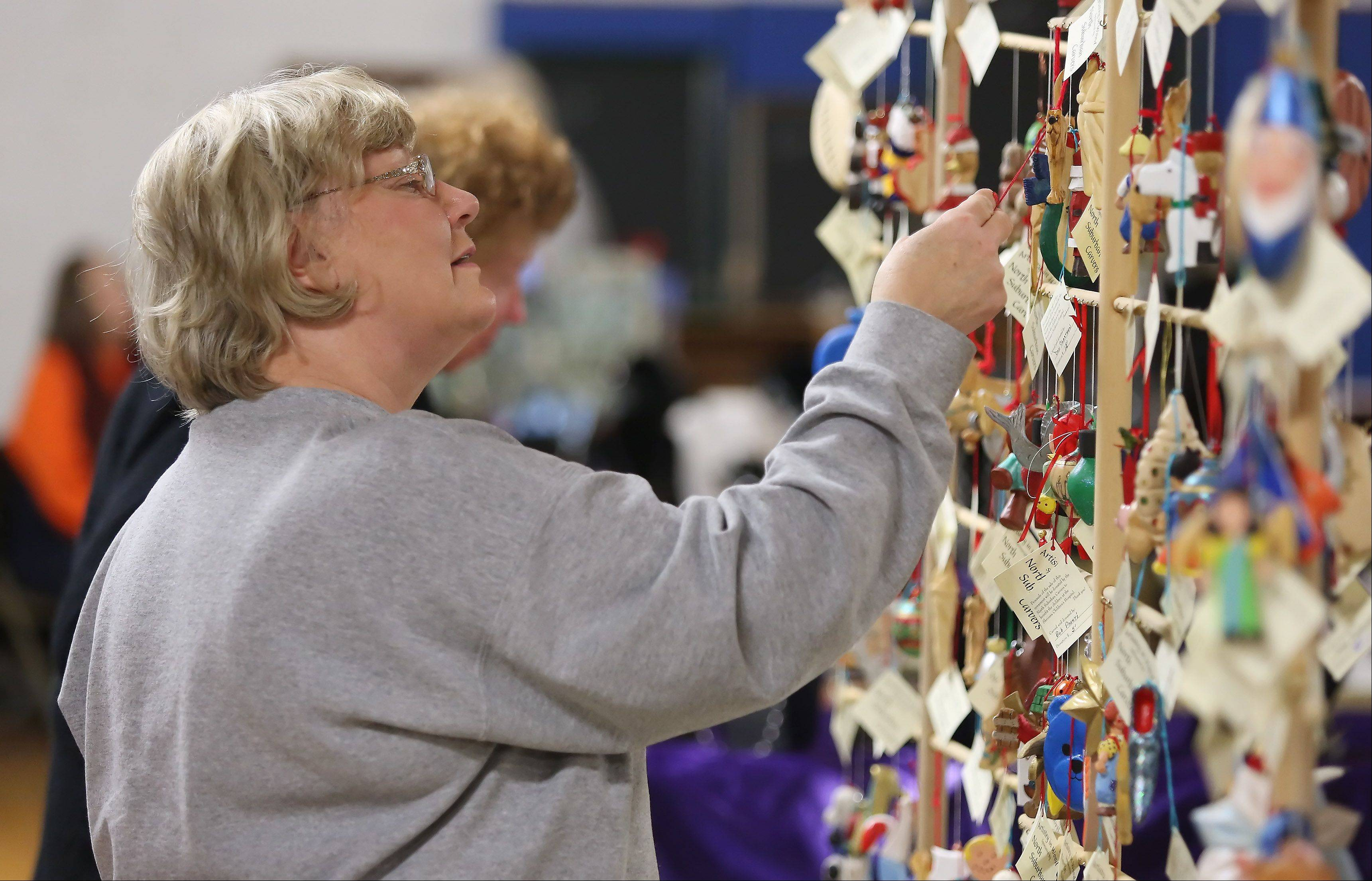 Libertyville resident Sylvia LeJeune looks at ornaments made by North Suburban Carvers during Island Lake�s 27th annual Holiday Craft Fair Sunday at the Island Lake Village Hall. The fair featured almost 45 vendors offering crafts, jewelry, gifts, clothing and more. On Sunday, Santa Claus met with children and adults alike to spread holiday cheer.