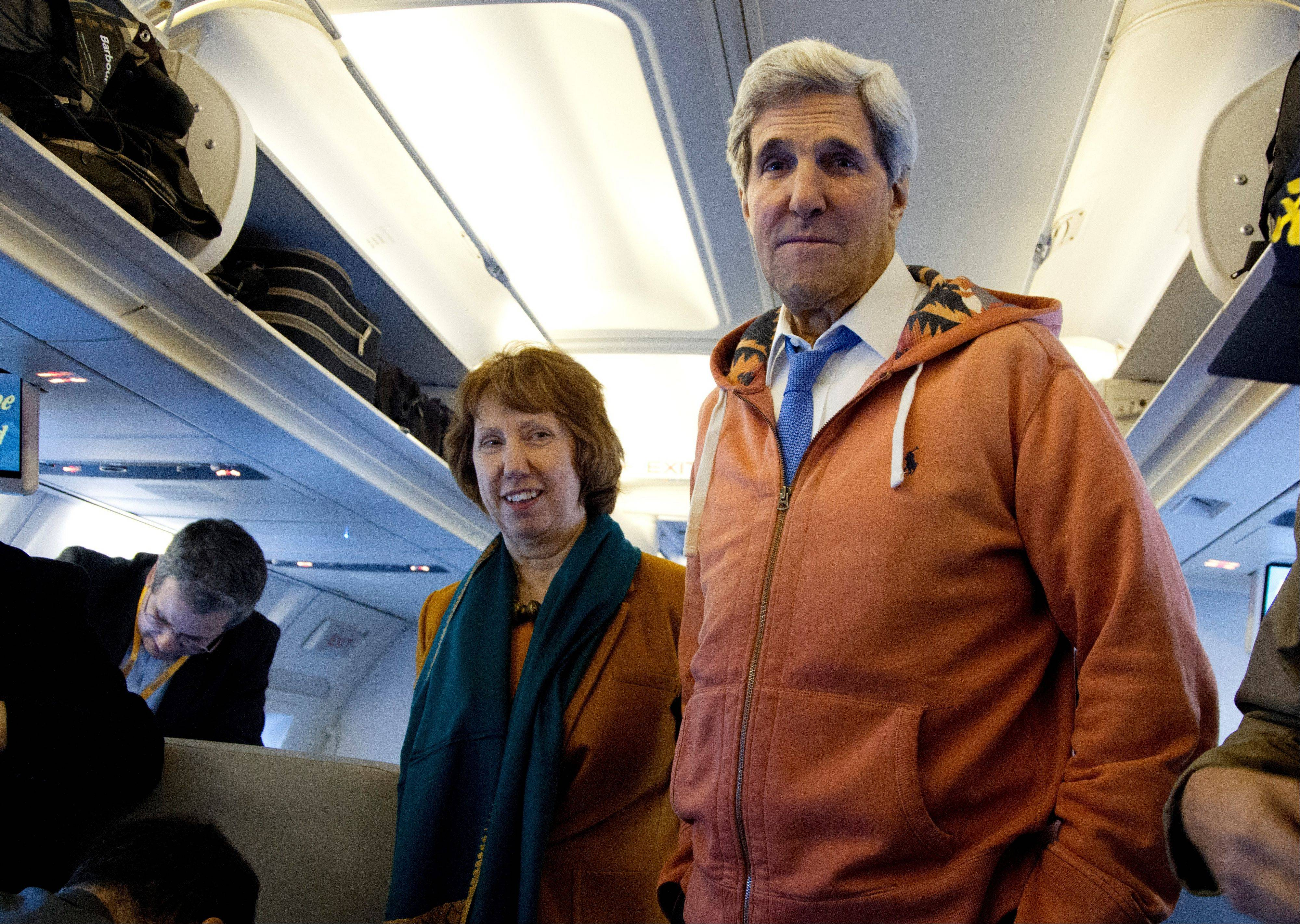U.S. Secretary of State John Kerry, right, and EU foreign policy chief Catherine Ashton, left, visit the media seating area of Kerry's aircraft as it sits on the tarmac at Geneva International airport before leaving for London, Sunday, in Geneva, Switzerland. A deal has been reached between six world powers and Iran that calls on Tehran to limit its nuclear activities in return for sanctions relief, the French and Iranian foreign ministers said early Sunday.