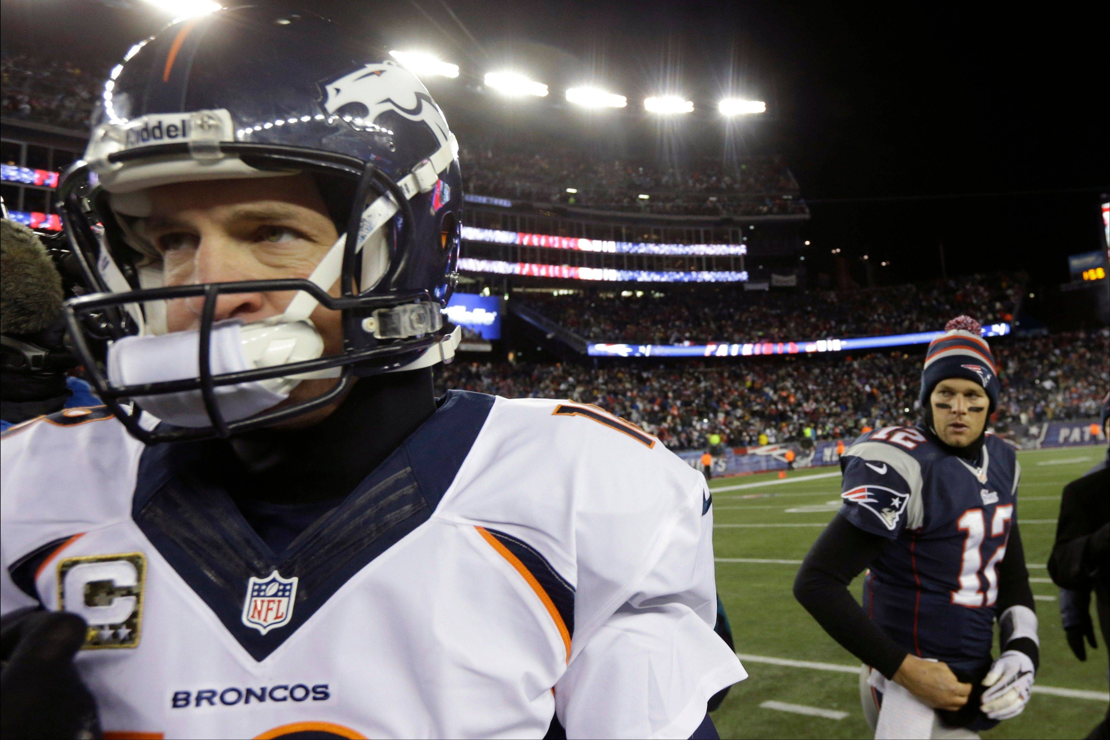 Denver Broncos quarterback Peyton Manning, left, walks away from New England Patriots quarterback Tom Brady after an NFL football game early Monday, Nov. 25, 2013, in Foxborough, Mass. The Patriots won 34-31 in overtime.