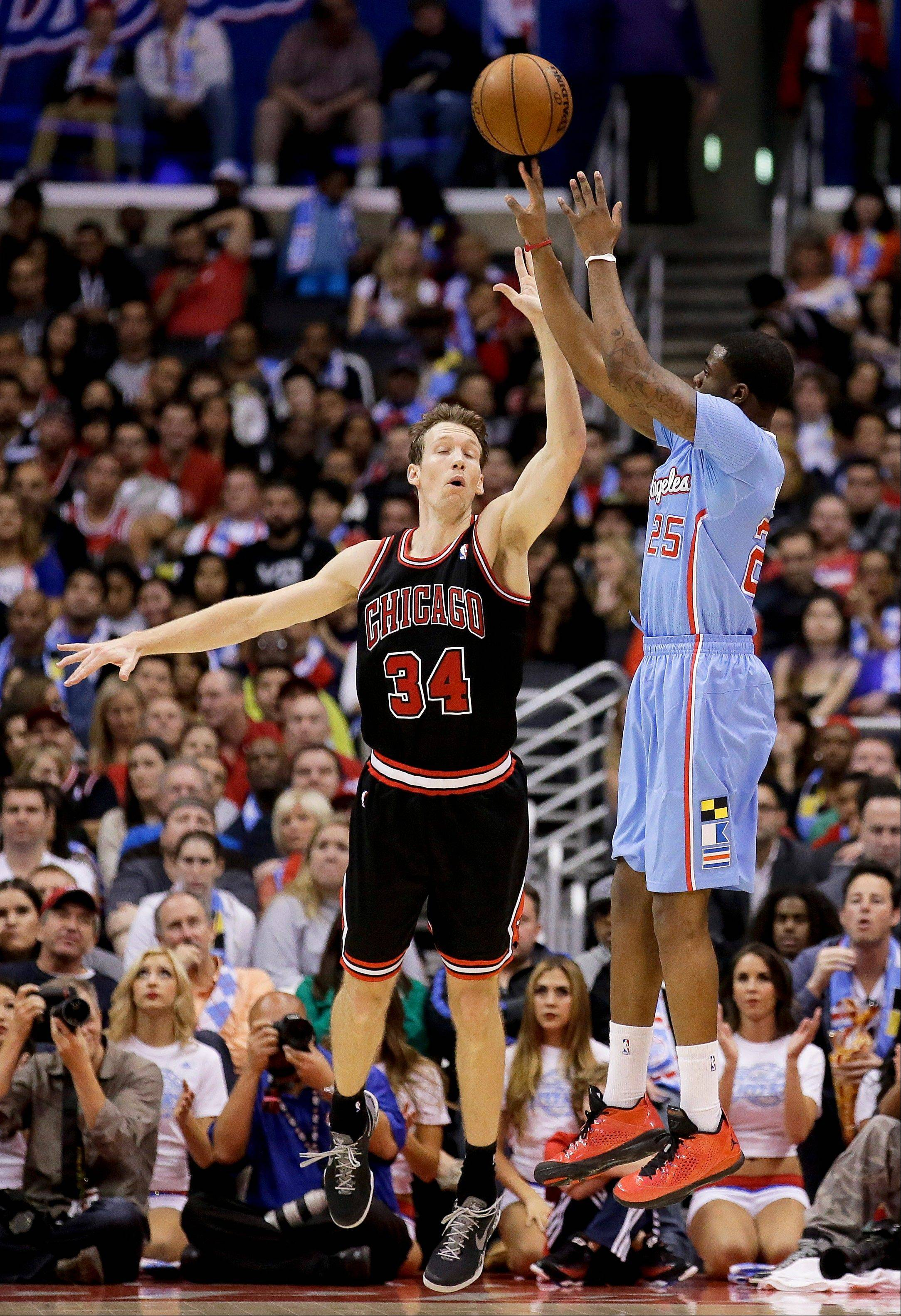 Los Angeles Clippers guard Reggie Bullock, right, scores over Chicago Bulls forward Mike Dunleavy during the second half of an NBA basketball game in Los Angeles, Sunday, Nov. 24, 2013. The Clippers won 121-82.