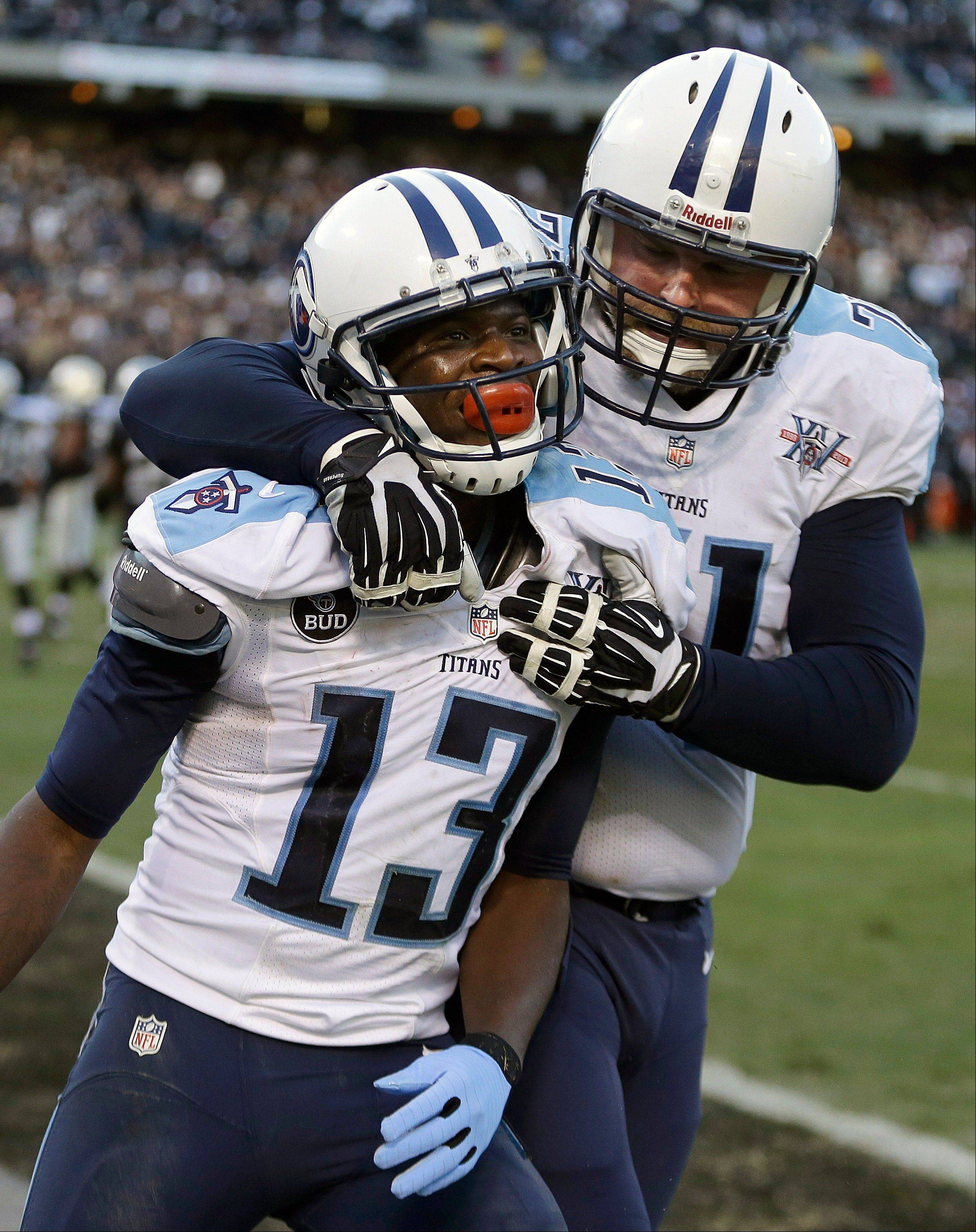 Tennessee Titans wide receiver Kendall Wright (13) celebrates with tackle Michael Roos after scoring on a 10-yard touchdown pass against the Oakland Raiders during the fourth quarter of an NFL football game in Oakland, Calif., Sunday, Nov. 24, 2013. The Titans won 23-19.