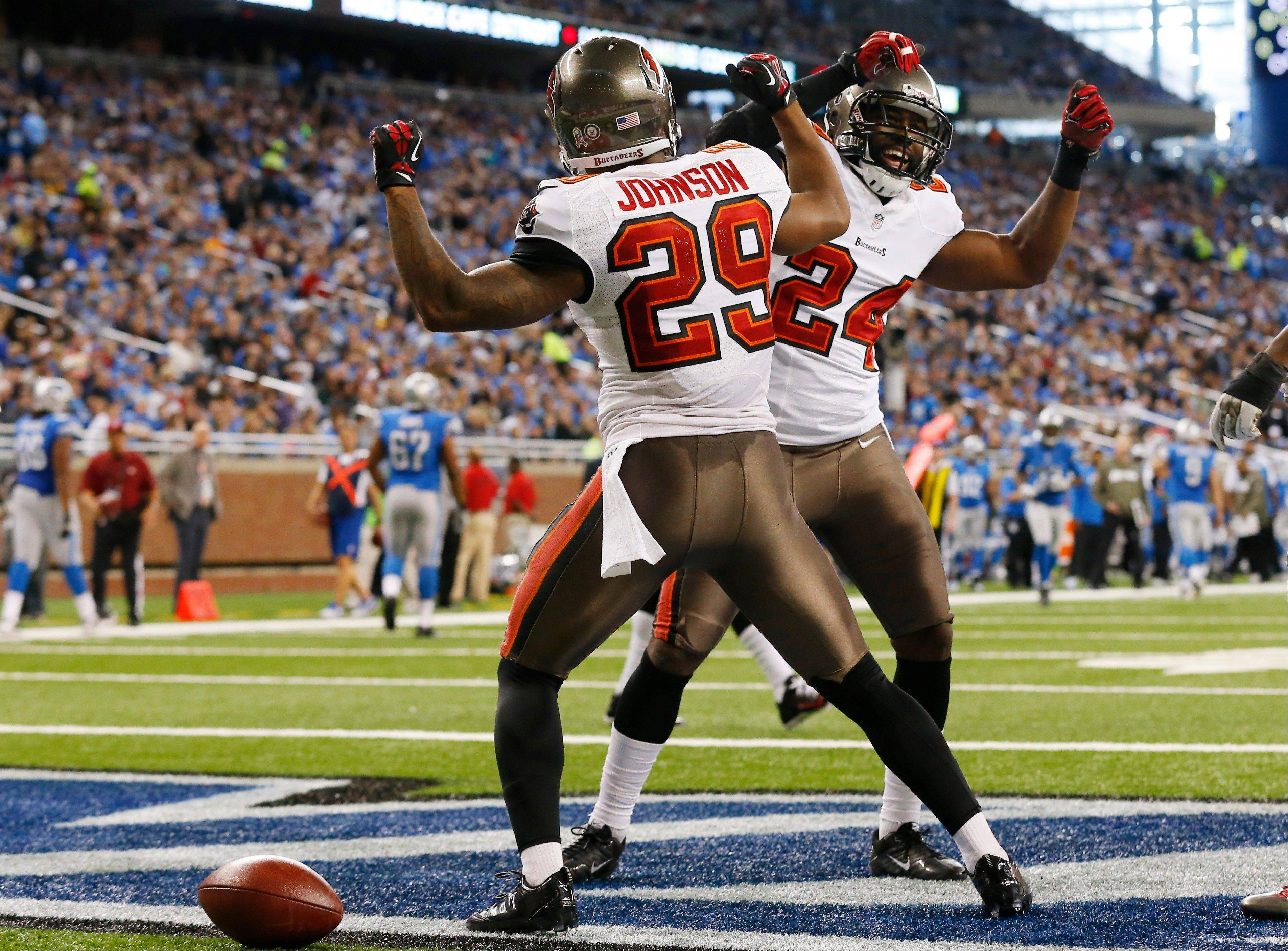 Tampa Bay Buccaneers cornerback Leonard Johnson (29) celebrates his 48-yard interception for a touchdown with teammate Darrelle Revis during the first half of an NFL football game against the Detroit Lions at Ford Field in Detroit, Sunday, Nov. 24, 2013.