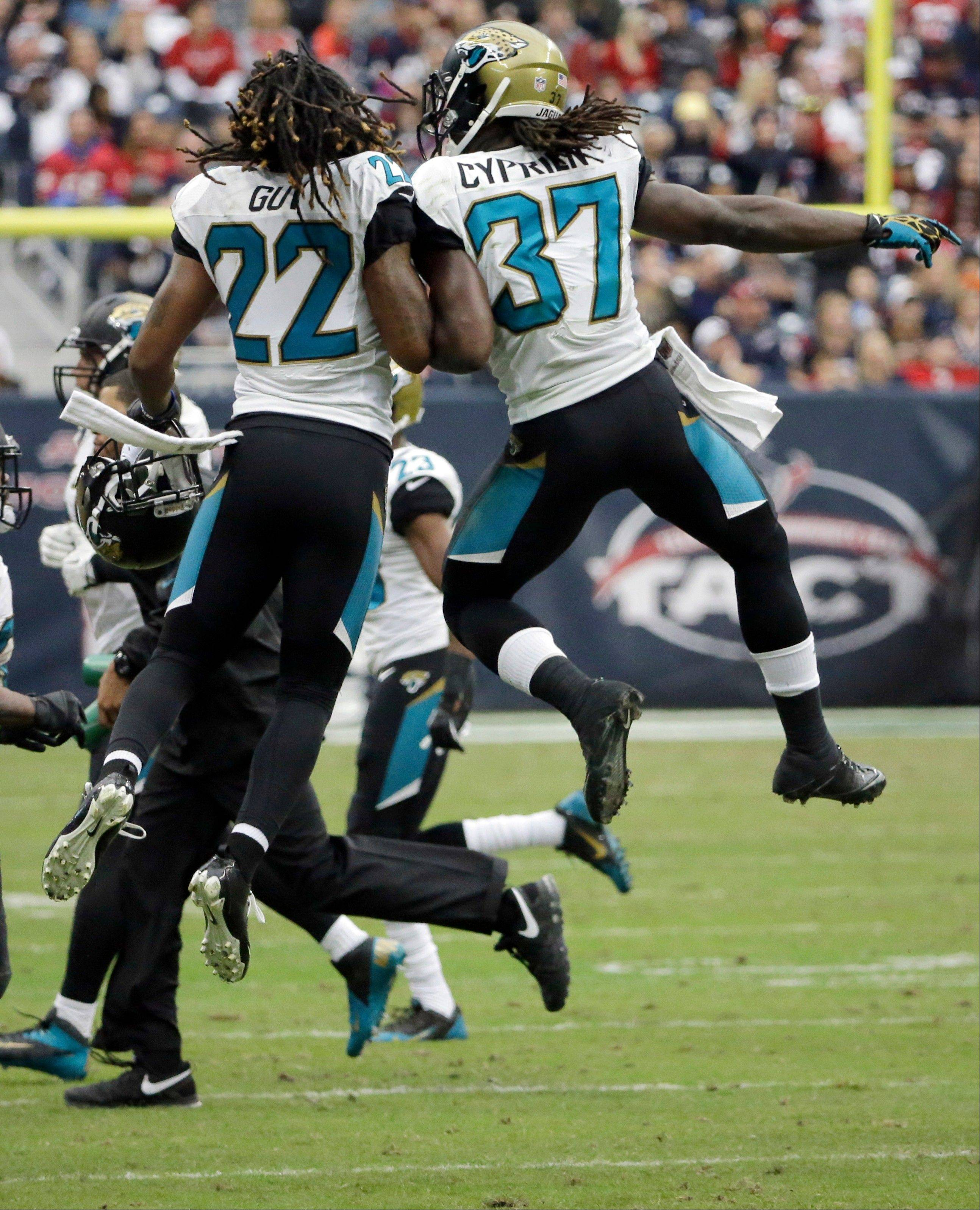 The Jacksonville Jaguars, including Winston Guy (22) Johnathan Cyprien (37) and Roy Miller (97) celebrate after stopping the Houston Texans on fourth down. during the fourth quarter of an NFL football game Sunday, Nov. 24, 2013, in Houston.