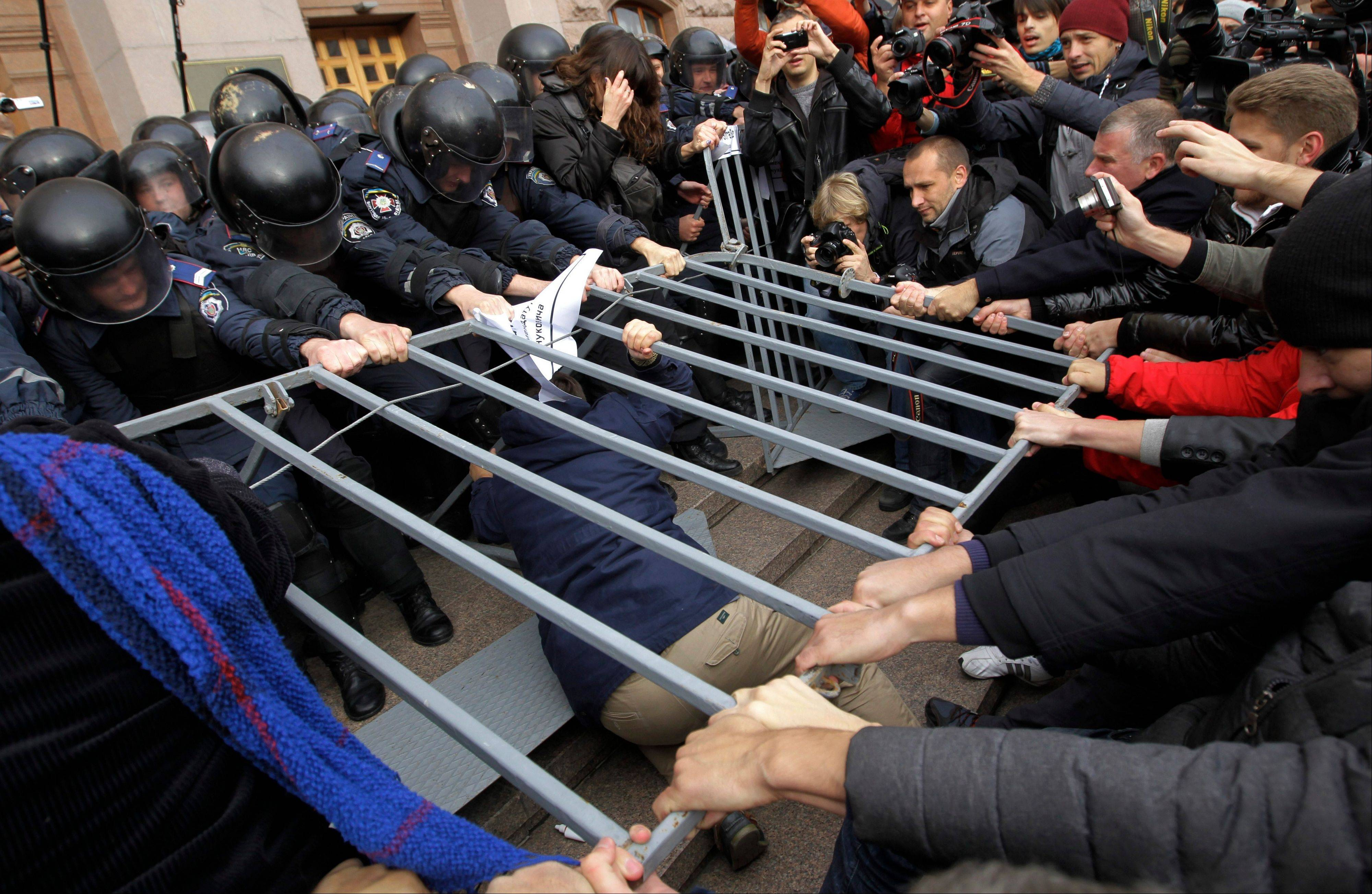 Opposition activists tussle with riot police outside the Kiev city council building during a protest rally demanding a re-election of the city council.