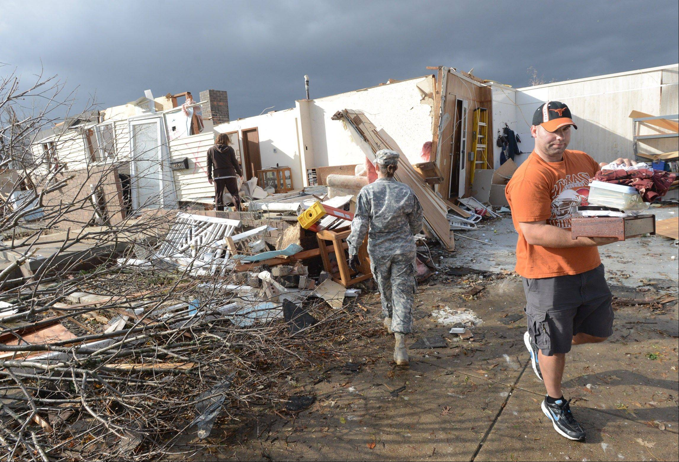 US Army National Guard Master Sergeant Katie Williams of Altamont, center, walks to a destroyed home of Barb and John Evans in the Devonshire Subdivision in Washington, Illinois as relatives rescue belongings after a tornado destroyed several homes on Sunday, Nov. 17, 2013.