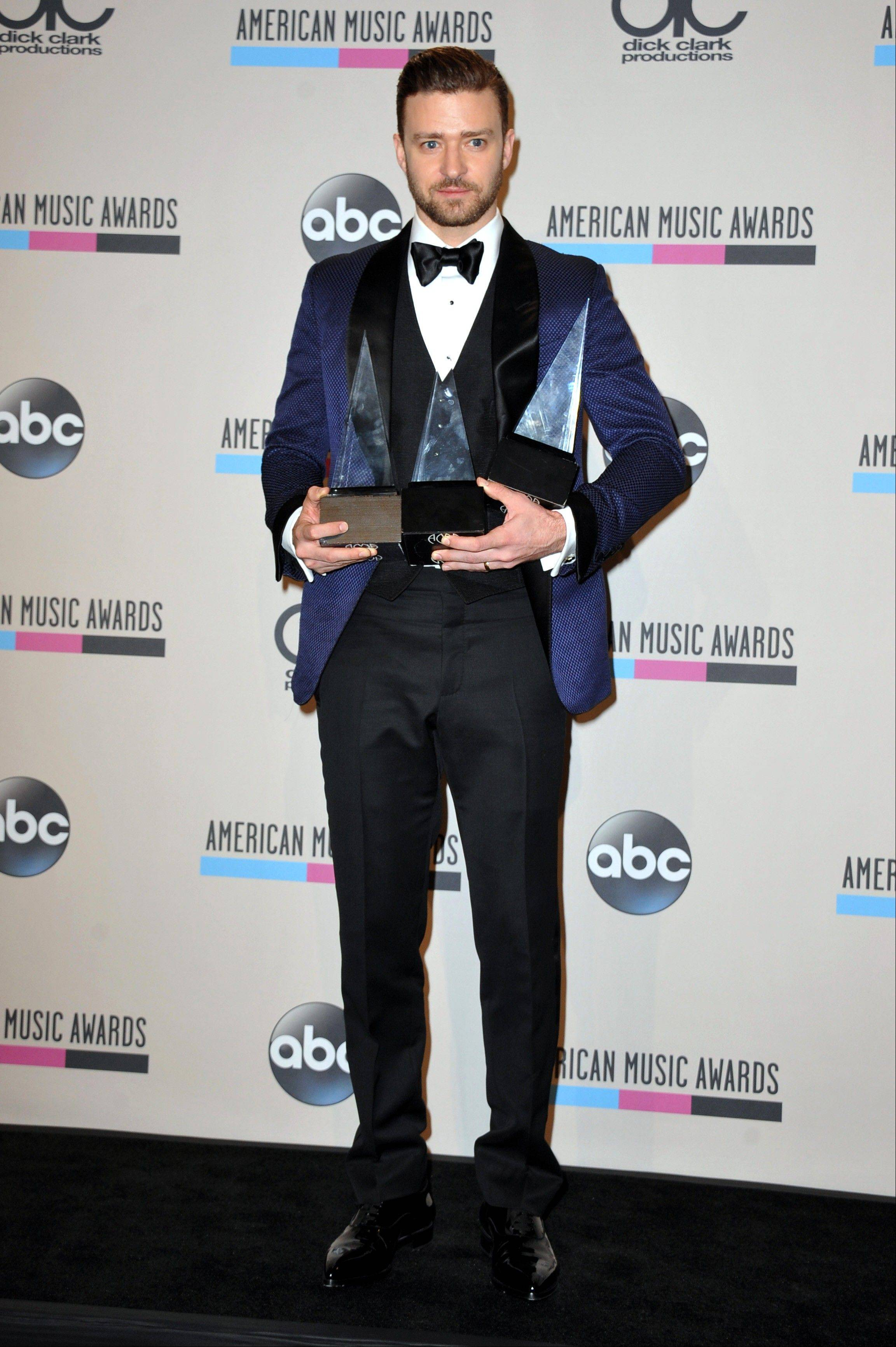 "Justin Timberlake poses backstage with his awards for favorite male artist - pop/rock, favorite male artist - soul/R&B, and favorite album - soul/R&B for ""The 20/20 Experience"" at the American Music Awards at the Nokia Theatre L.A. Live on Sunday, Nov. 24, 2013, in Los Angeles. (Photo by Jordan Strauss/Invision/AP)"