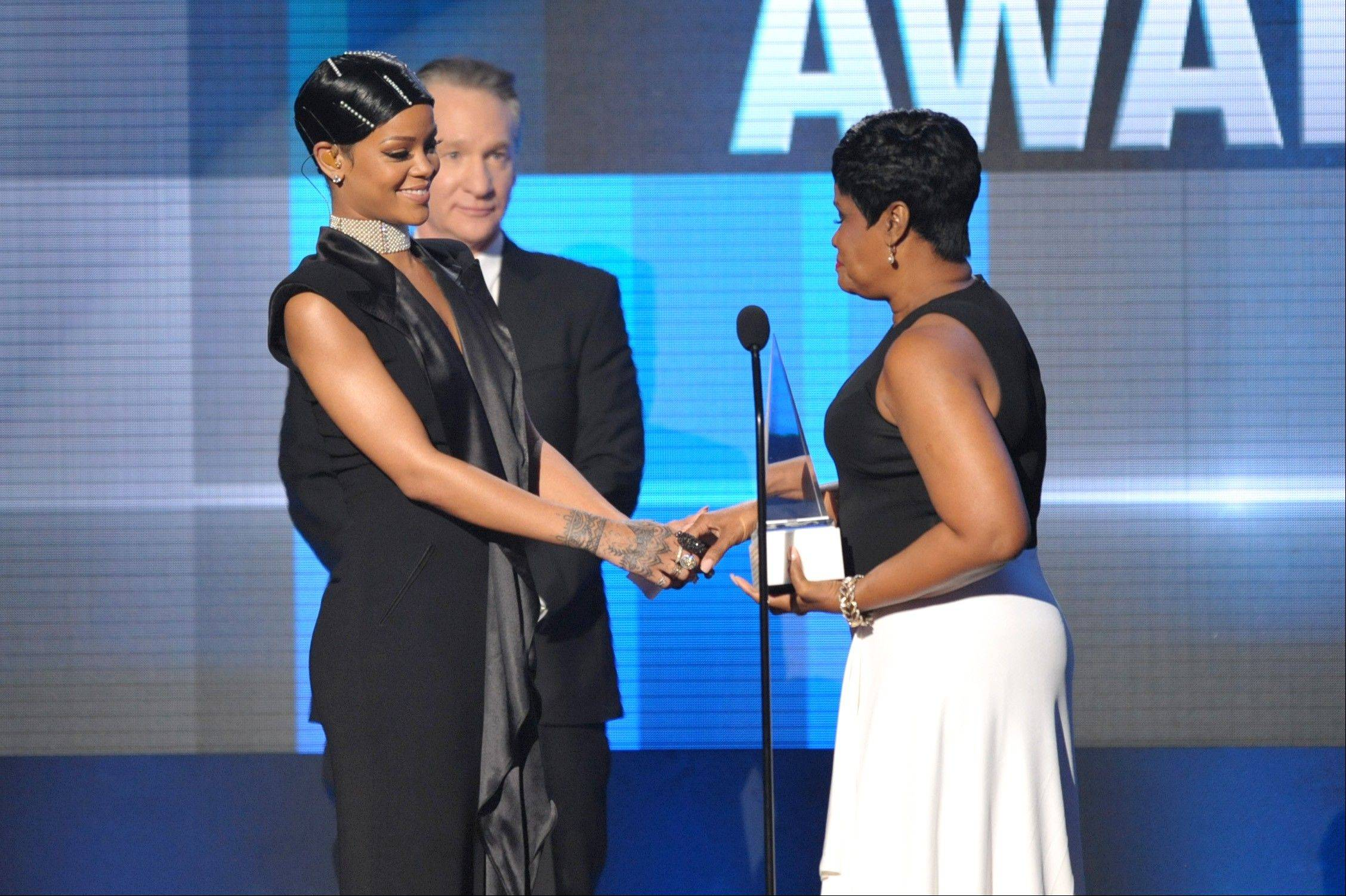 Monica Braithwaite, right, presents the Icon award to her daughter Rihanna on stage at the American Music Awards at the Nokia Theatre L.A. Live on Sunday, Nov. 24, 2013, in Los Angeles. (Photo by John Shearer/Invision/AP)