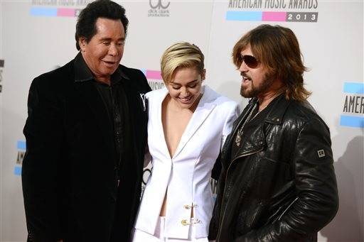 Wayne Newton, left, joins Miley Cyrus and her father, Billy Ray Cyrus on the red carpet at the American Music Awards.