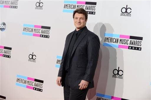 """Firefly"" and ""Castle"" actor Nathan Fillion is all smiles as he makes his way into the awards show. Fillion even managed to tweet something about Lady Gaga's unusual arrival style."
