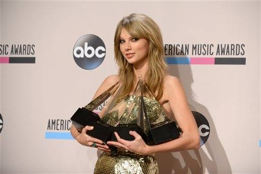 Taylor Swift holds her four awards including one for artist of the year backstage at the AMAs.
