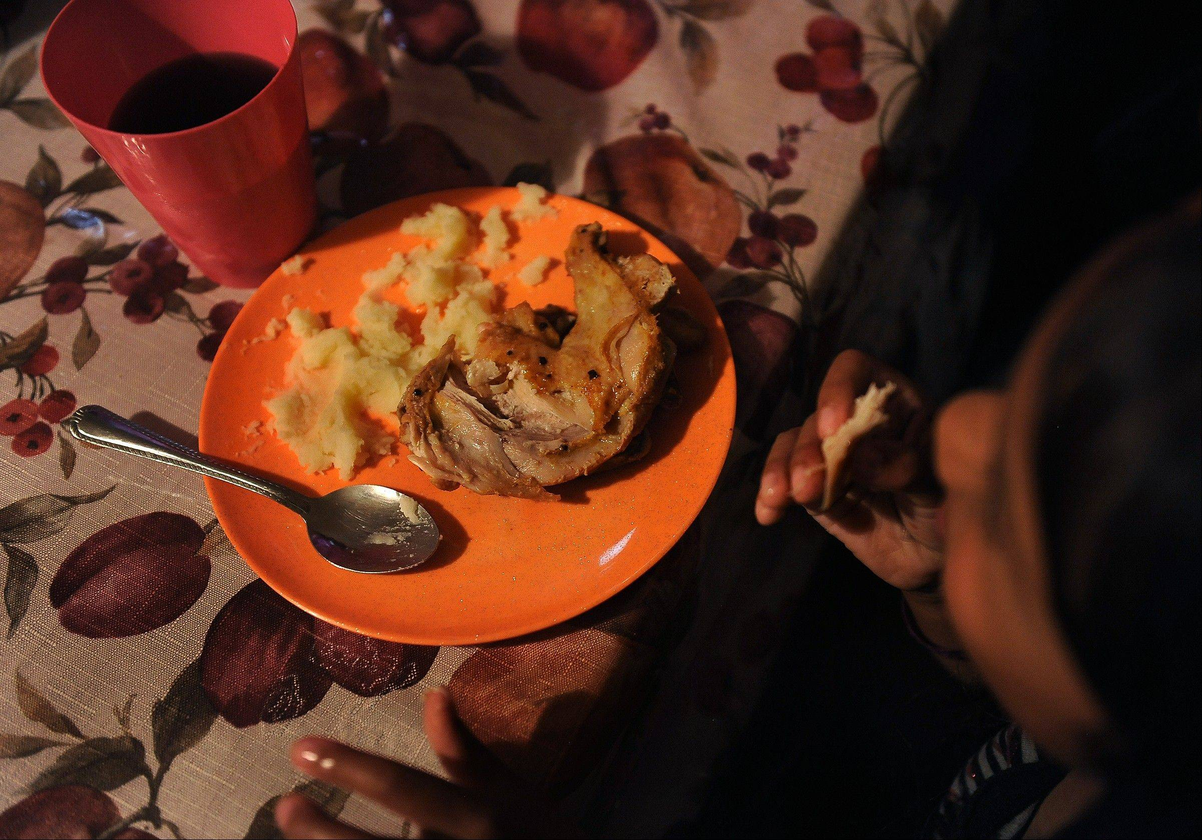 Jocelynn Banda, 6, eats chicken and mashed potatoes made by her mother for dinner.