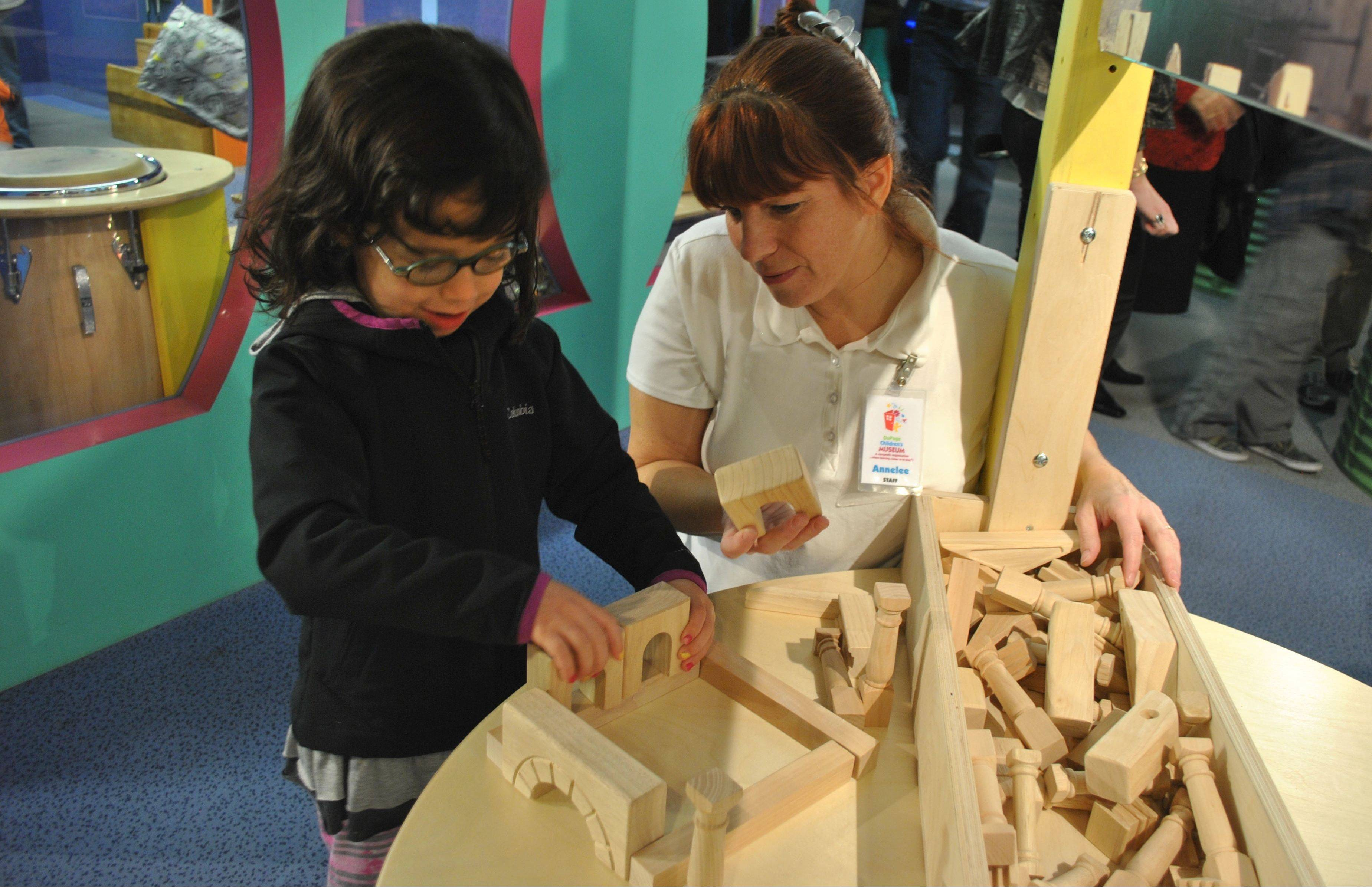 Staffers guide children as they build their own monuments at a new exhibit at the DuPage Children's Museum.