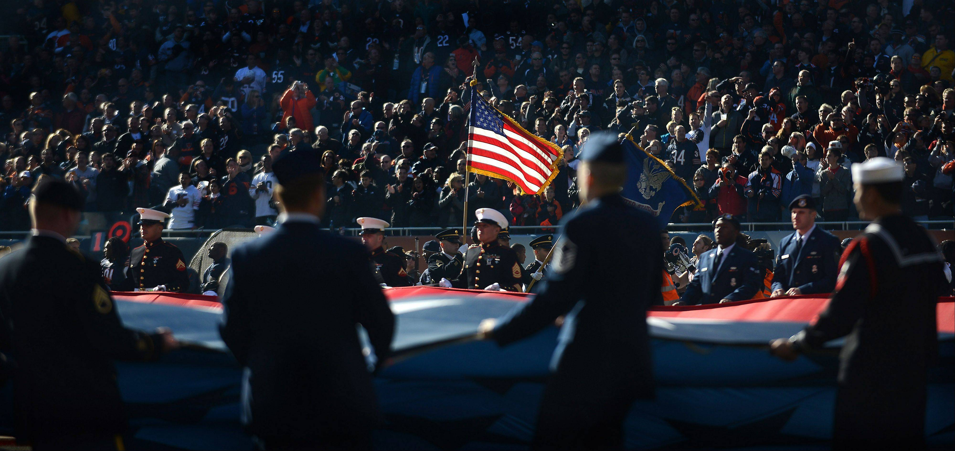 The Bears game against the Lions was held the day before Veterans Day and I had seen the huge American flag they were bringing out in the tunnel earlier. Fortunately the sun was coming in at a severe angle that put much of the stands in shadow, partly silhouetted the servicemen and women in front of me and highlighted a flag being held by the color guard. This photo was published in the weekly Perspective column in the print edition.
