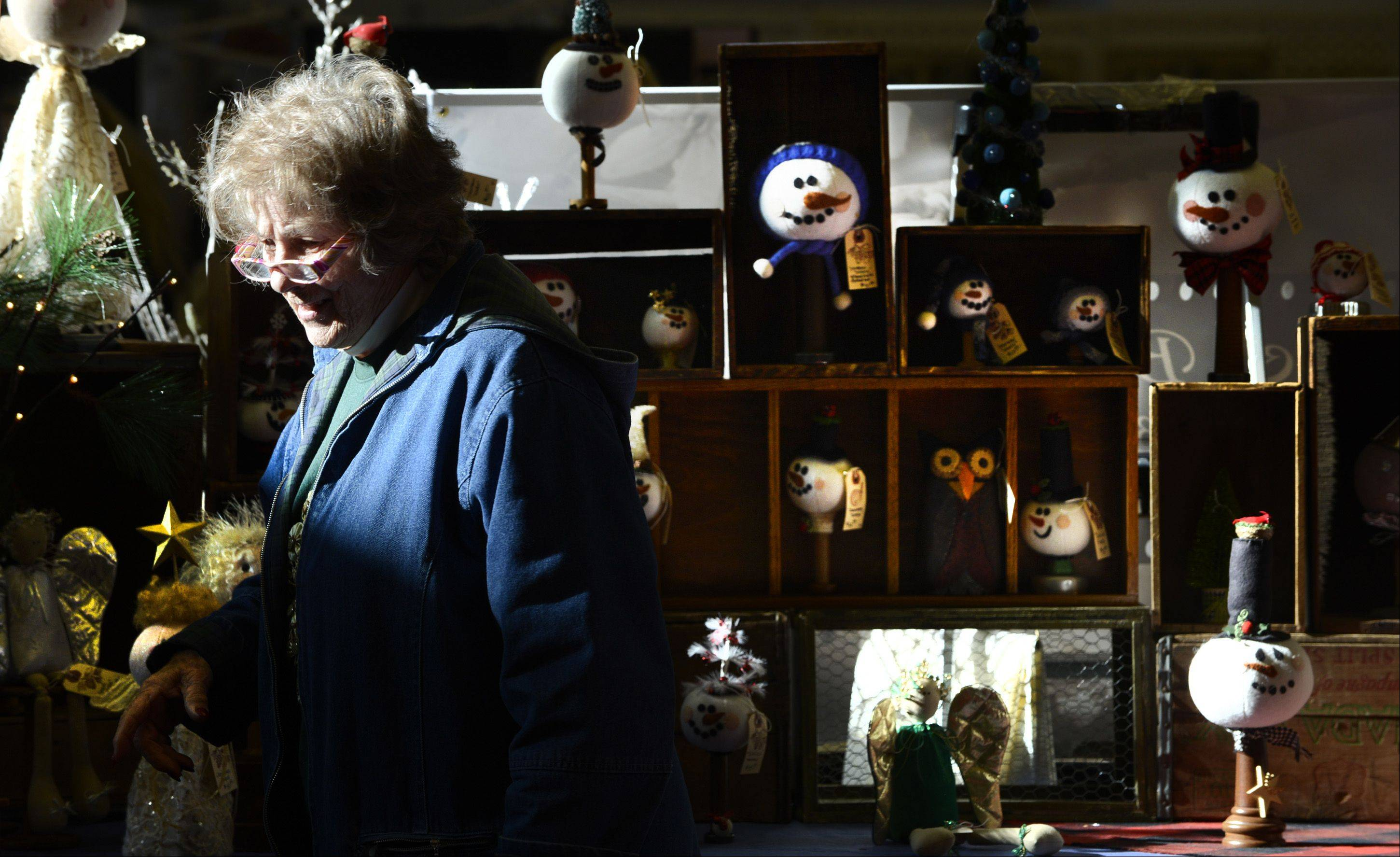 "Elaine Hicks, of Elk Grove Village, browses the merchandise of Kathie Roller's booth Sunday at the Christmas on the Fox Arts and Crafts Show at the Kane County Fairgrounds in St. Charles. ""This is better than anything Hallmark has got,"" said Hicks. ""These are real crafts."""
