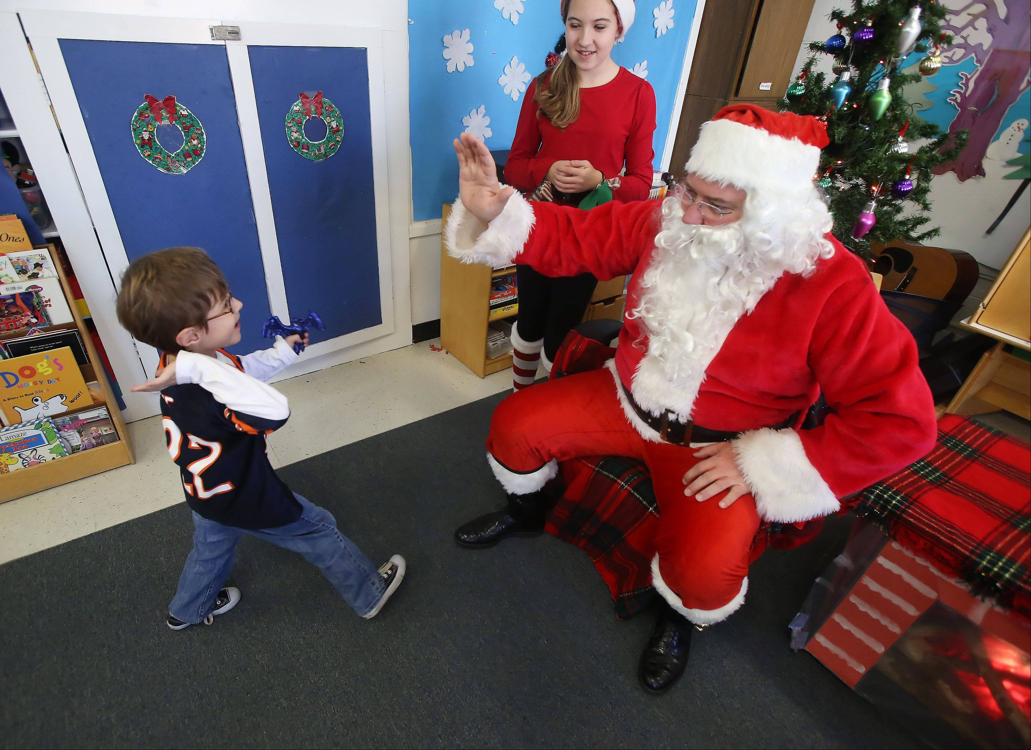 Five-year-old Conor Cook of Prairie Grove comes over to high five Santa Claus (Island Lake Trustee Keith Johns) Sunday during Island Lake's 27th Annual Holiday Craft Fair Sunday at the Island Lake Village Hall. The fair featured almost 45 vendors offering crafts, jewelry, gifts, clothing and more.
