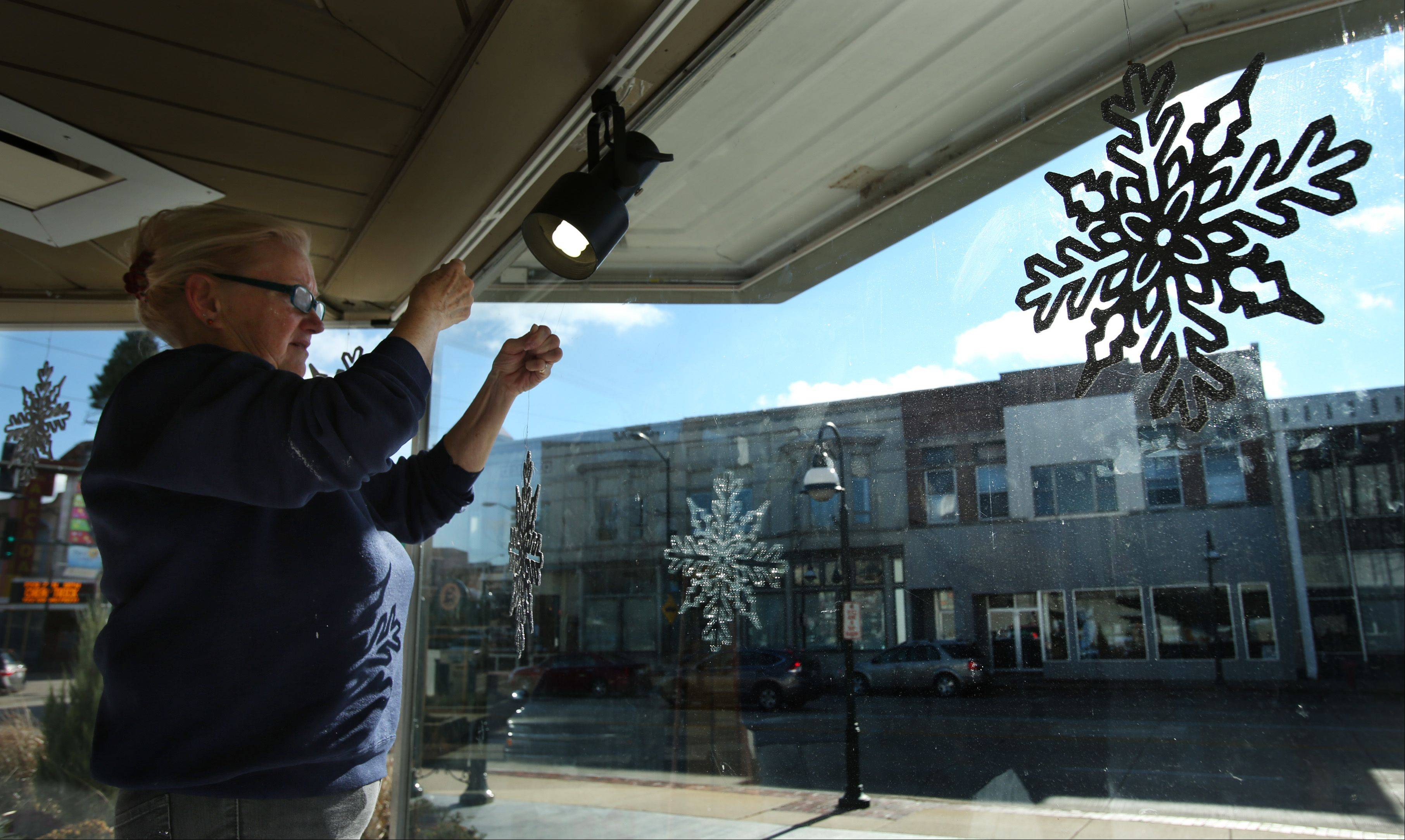 Volunteer Janet Wilson, of St. Charles, hangs snowflake decorations as she and fellow volunteer Darlene Riebe install a Christmas display Monday morning in the large window on the south side of the St. Charles Municipal Center. The display will promote the Holiday Homecoming event, sponsored by the Downtown St. Charles Partnership. Despite the chilly winds and cold temperatures Monday, both women were working up a good sweat in the display window as the sun continued to heat up their confined work space. Both women say it's even worse working inside that window in the summer.