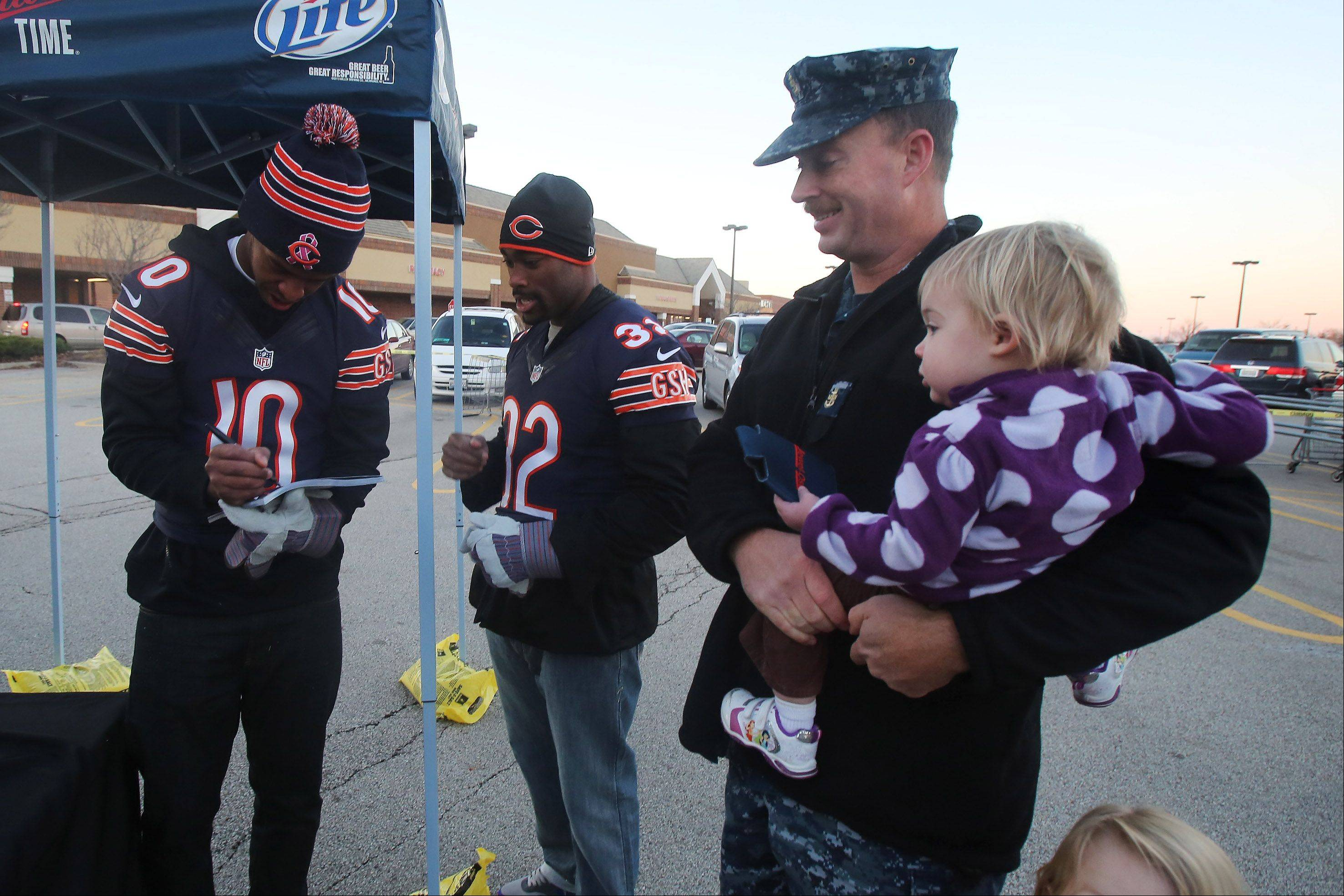 Navy Fire Control Chief Adam Acker holds his daughter Emily as he gets autographs from Chicago Bears rookies Marquess Wilson and Michael Ford as veterans and their families received Thanksgiving meals and met Bears players at Jewel Osco in Gurnee on Monday. MillerCoors teamed up with Operation Homefront, the Chicago Bears, Bears Care, and Jewel Osco to donate turkeys and side dishes to 400 military families over two days.