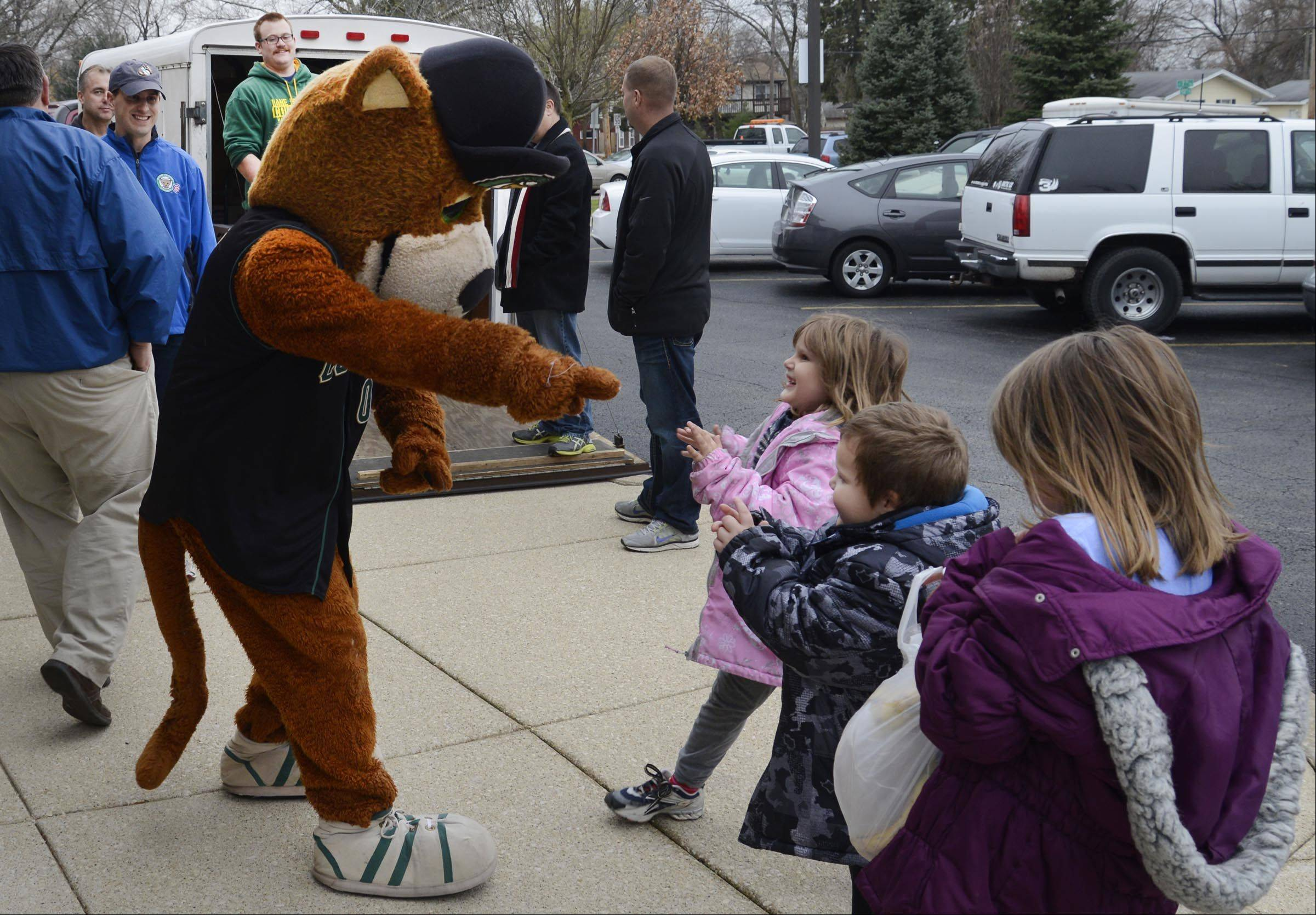Kane County Cougars mascot Ozzie T. Cougar goofs around with children as the baseball team's staff assists the Salvation Army Tri-City corps in handing out frozen turkeys and chickens to more than 300 families in need Thursday at the Joe K. Anderson Community Center in St. Charles.