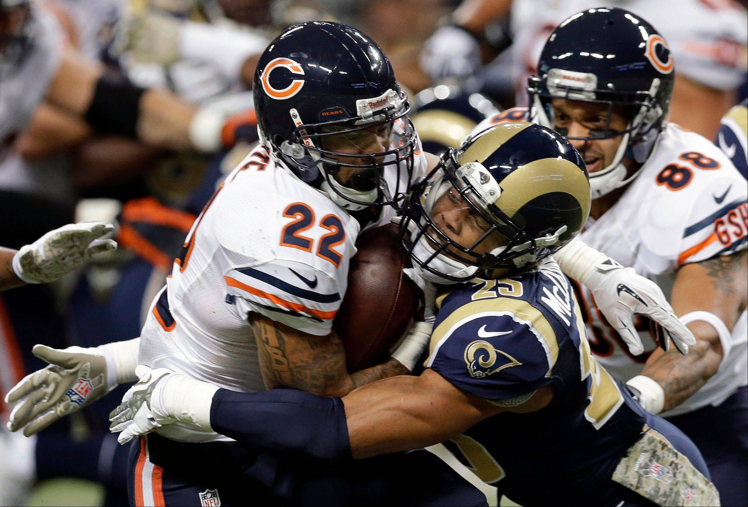 Chicago Bears running back Matt Forte, left, runs with the ball as he is pulled down by St. Louis Rams safety T.J. McDonald during the first quarter.
