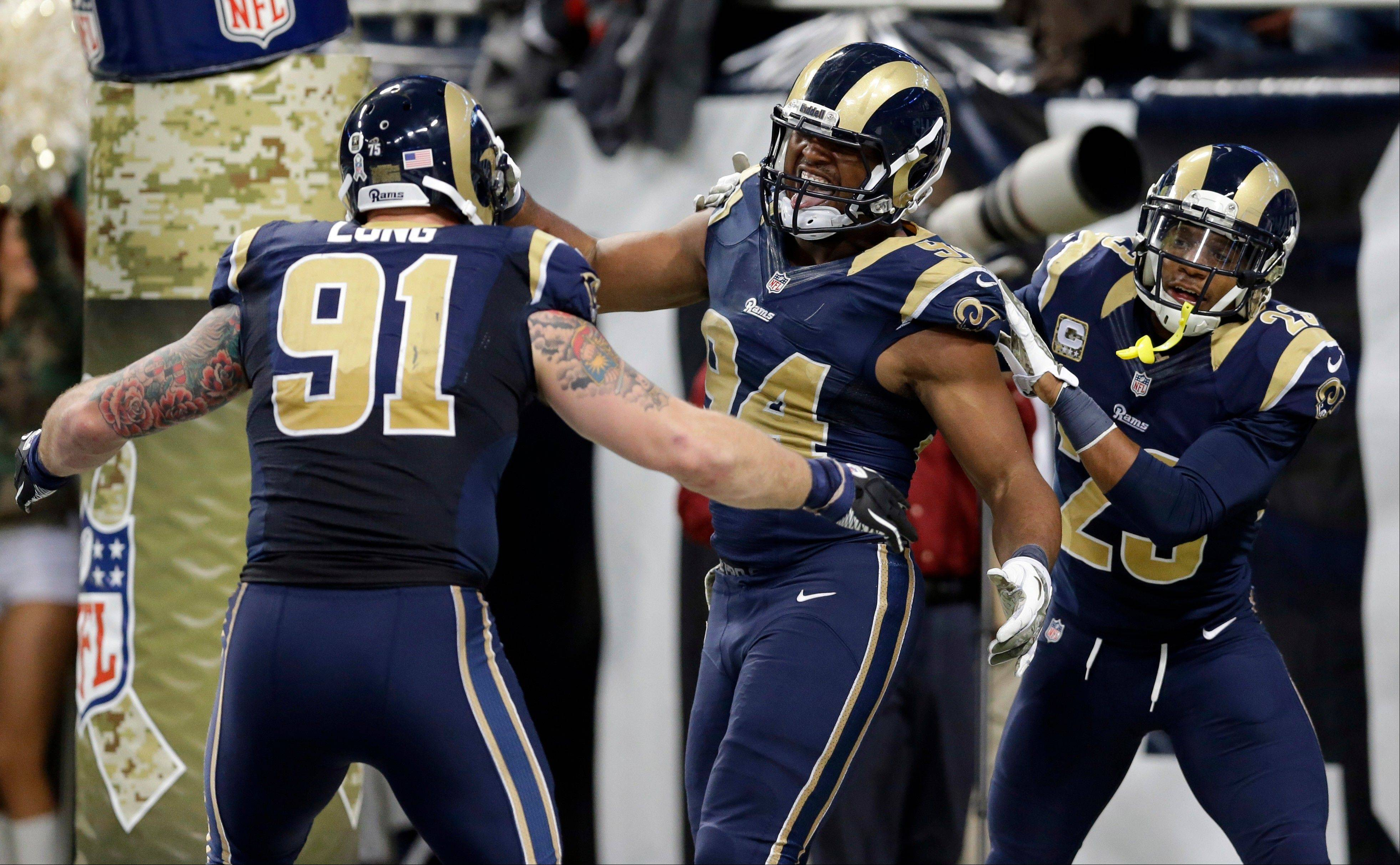St. Louis Rams defensive end Robert Quinn, center, is congratulated by teammates Chris Long, left, and Rodney McLeod after recovering a fumble by Chicago Bears quarterback Josh McCown and returning it 31-yard for a touchdown during the fourth quarter. The Rams won 42-21.