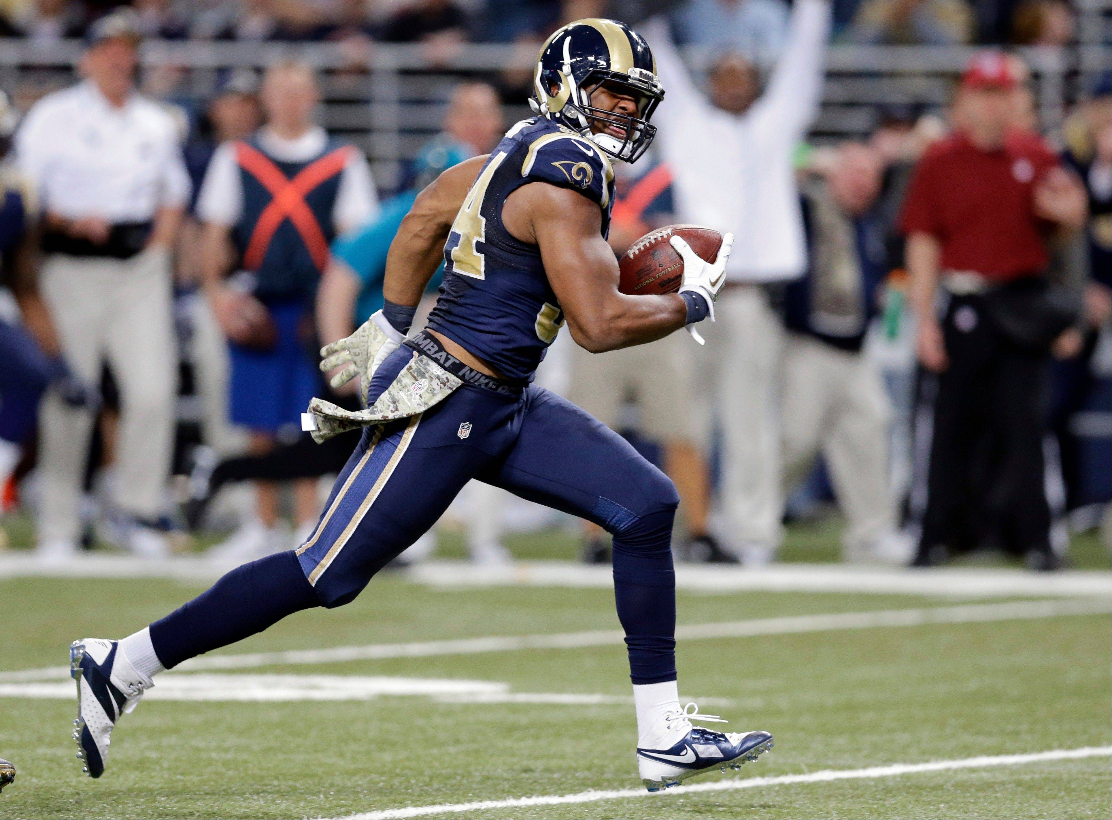 St. Louis Rams defensive end Robert Quinn runs the ball back 31 yards for a touchdown after recovering a fumble by Chicago Bears quarterback Josh McCown during the fourth quarter. The Rams won 42-21.