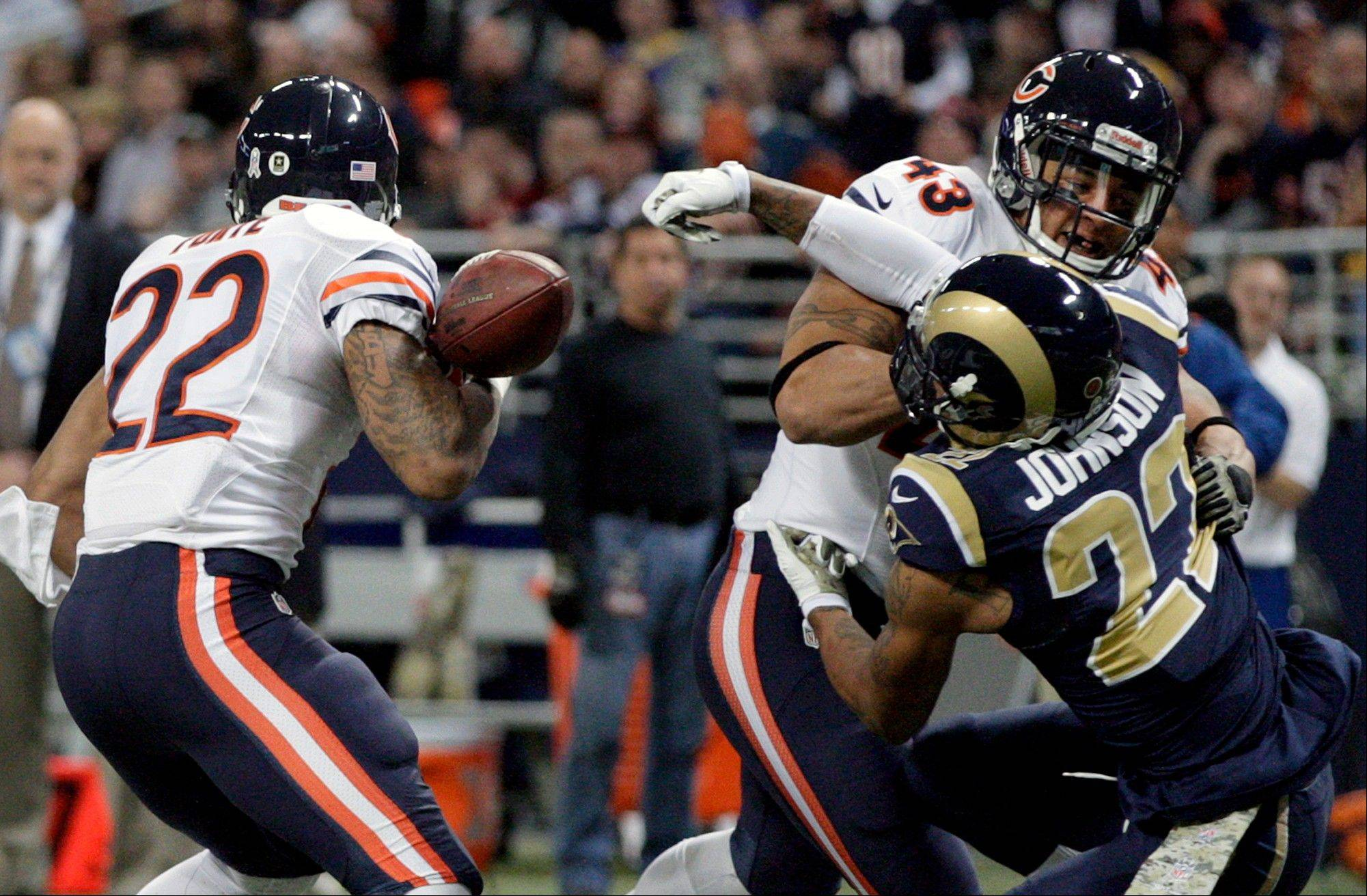 St. Louis Rams cornerback Trumaine Johnson, right, forces Chicago Bears running back Matt Forte, left, to fumble as Bears fullback Tony Fiammetta (43) watches during the first quarter. The Rams' James Laurinaitis recovered the fumble.