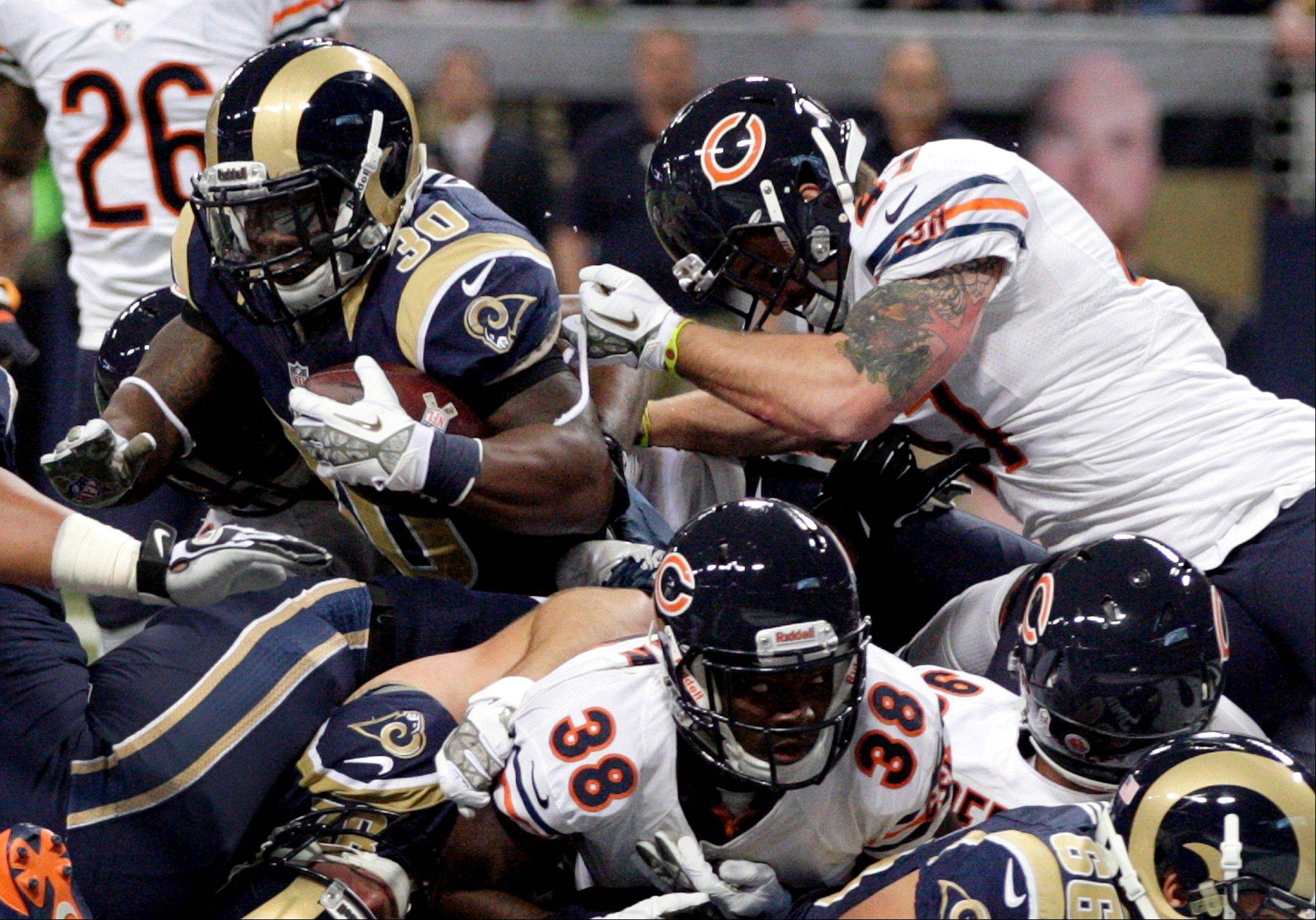St. Louis Rams running back Zac Stacy (30) scores on a 1-yard run as Chicago Bears safety Chris Conte, top right, and cornerback Zack Bowman (38) defend during the first quarter.