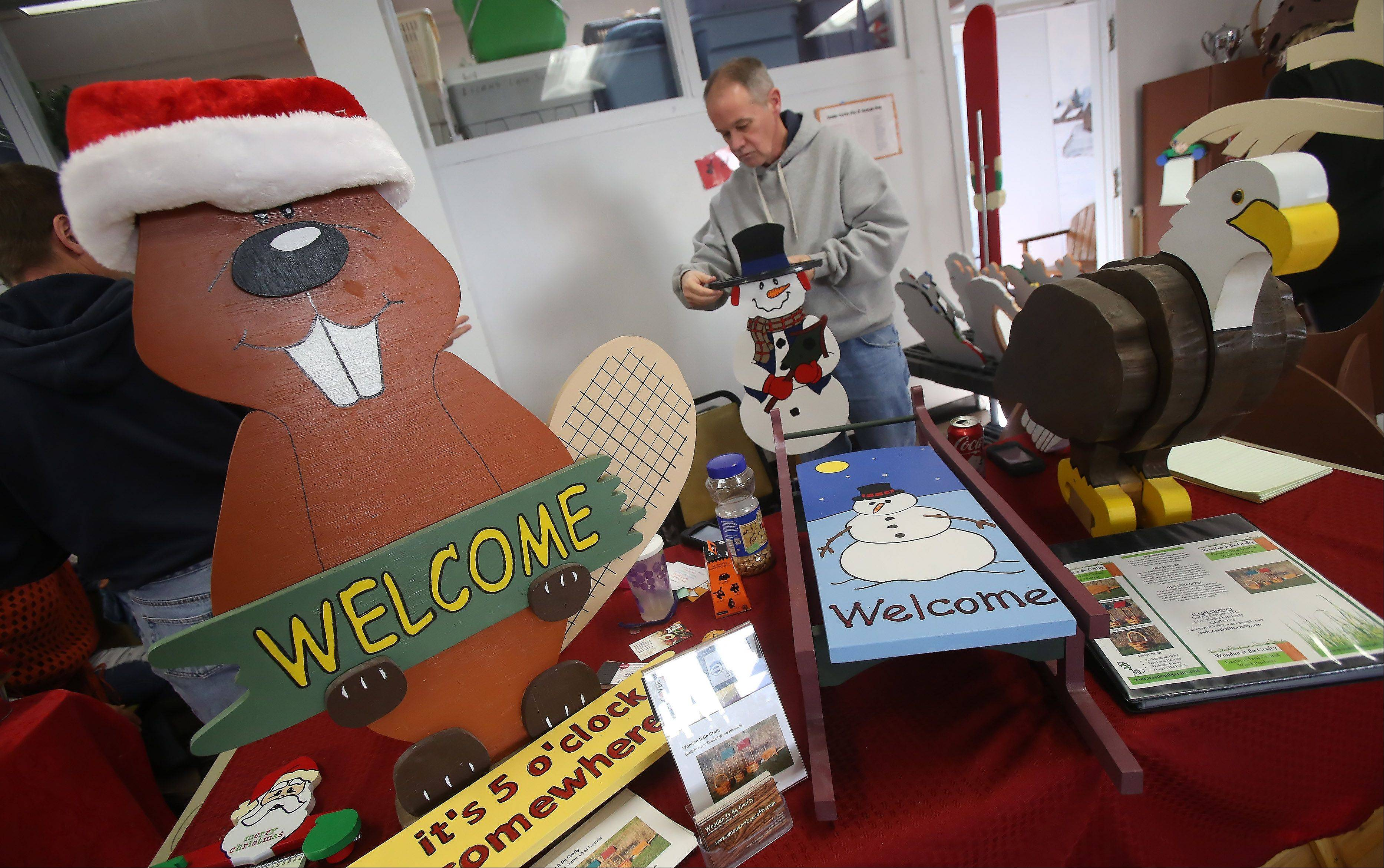 Crafter Mike Sikorski works on a sign at Wooden It Be Crafty during Island Lake's 27th annual Holiday Craft Fair Sunday at the Island Lake Village Hall. The fair featured almost 45 vendors offering crafts, jewelry, gifts, clothing and more. On Sunday, Santa Claus met with children and adults alike to spread holiday cheer.