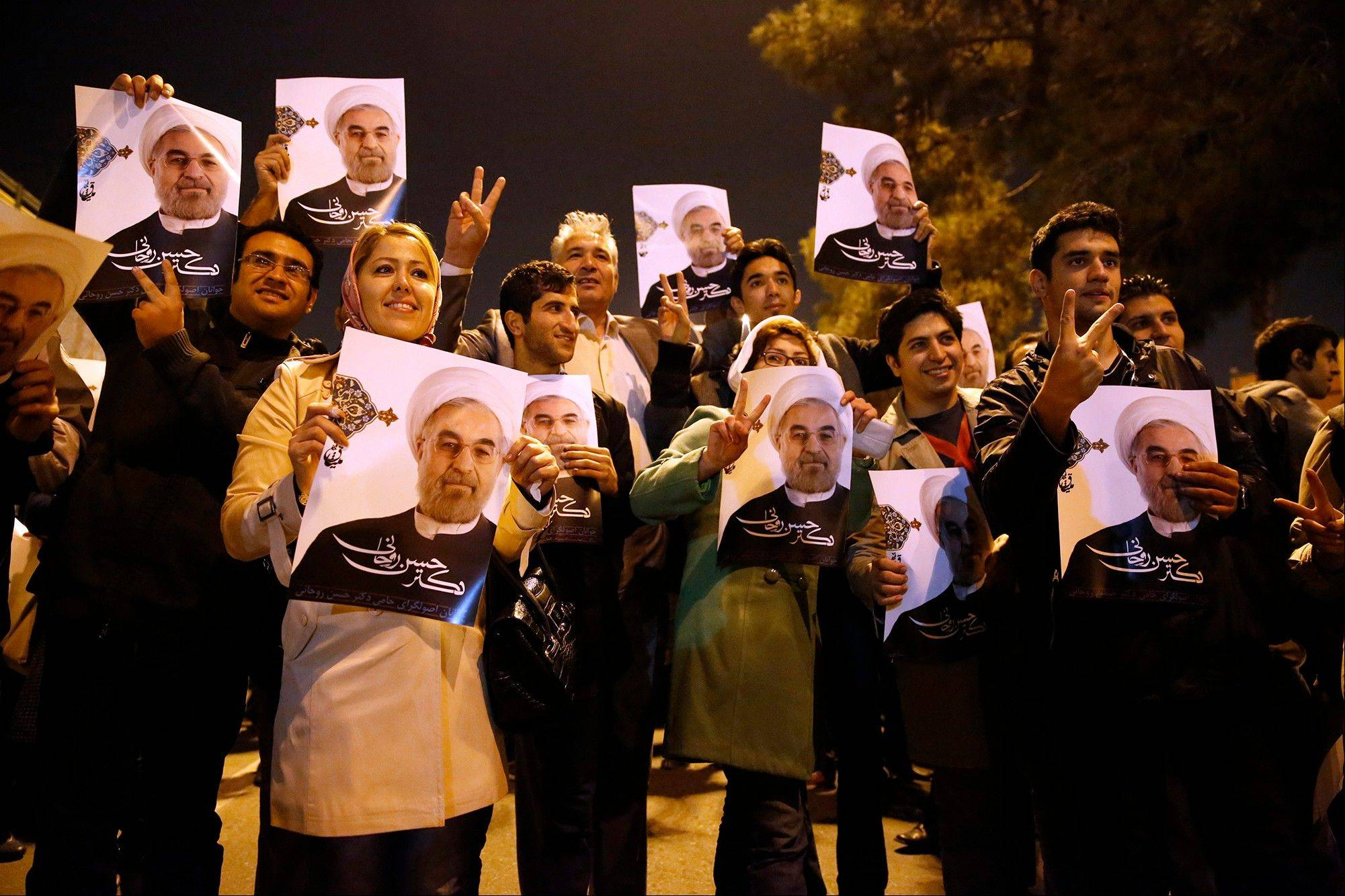 Iranians hold posters of President Hassan Rouhani as they welcome Iranian nuclear negotiators upon their arrival from Geneva at the Mehrabad airport in Tehran, Iran, Sunday.