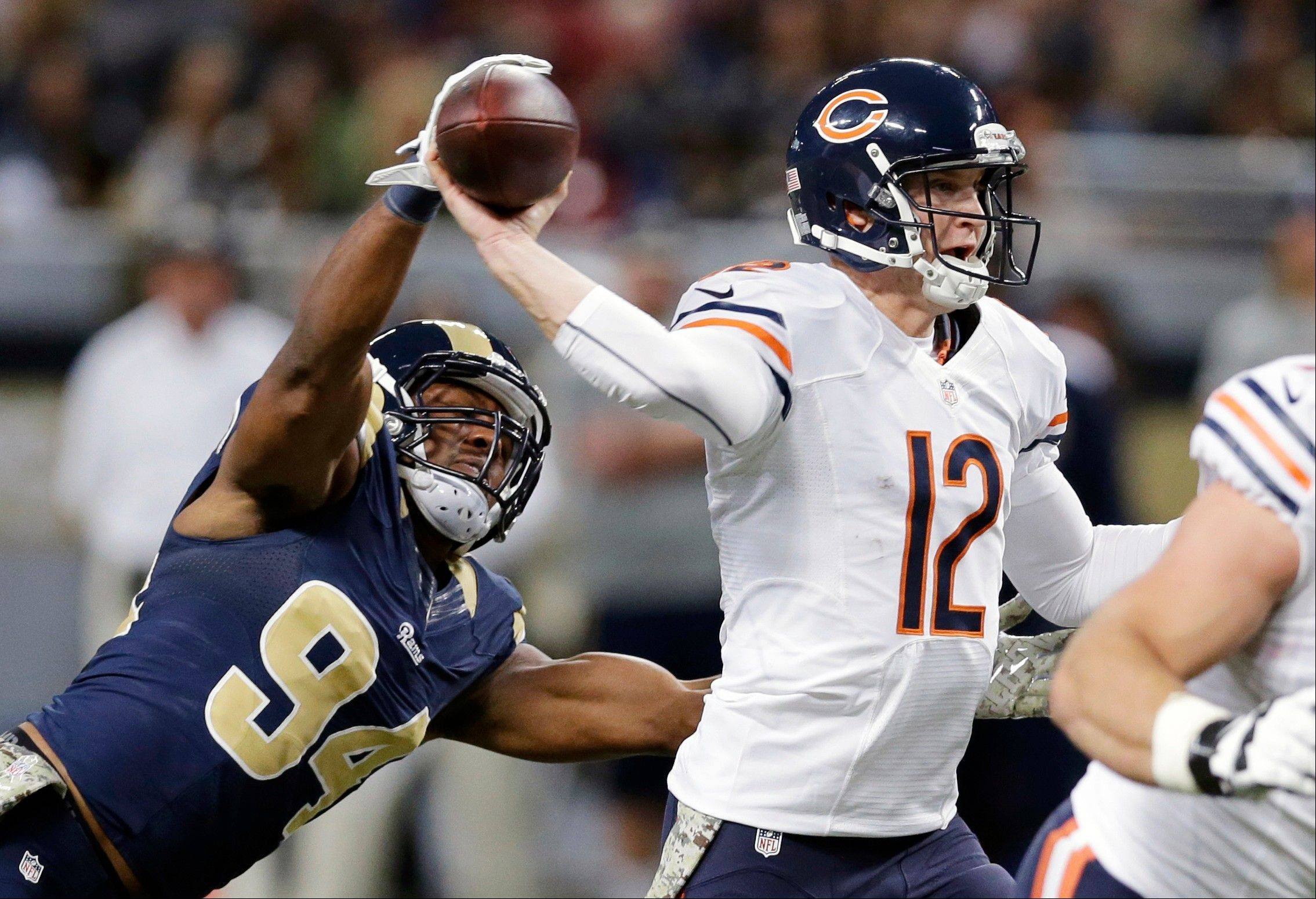 Rams defensive end Robert Quinn, left, gets his hand on the ball as Bears quarterback Josh McCown throws during the first quarter Sunday in St. Louis. McCown threw for 352 yards but let the Bears to just 21 points.