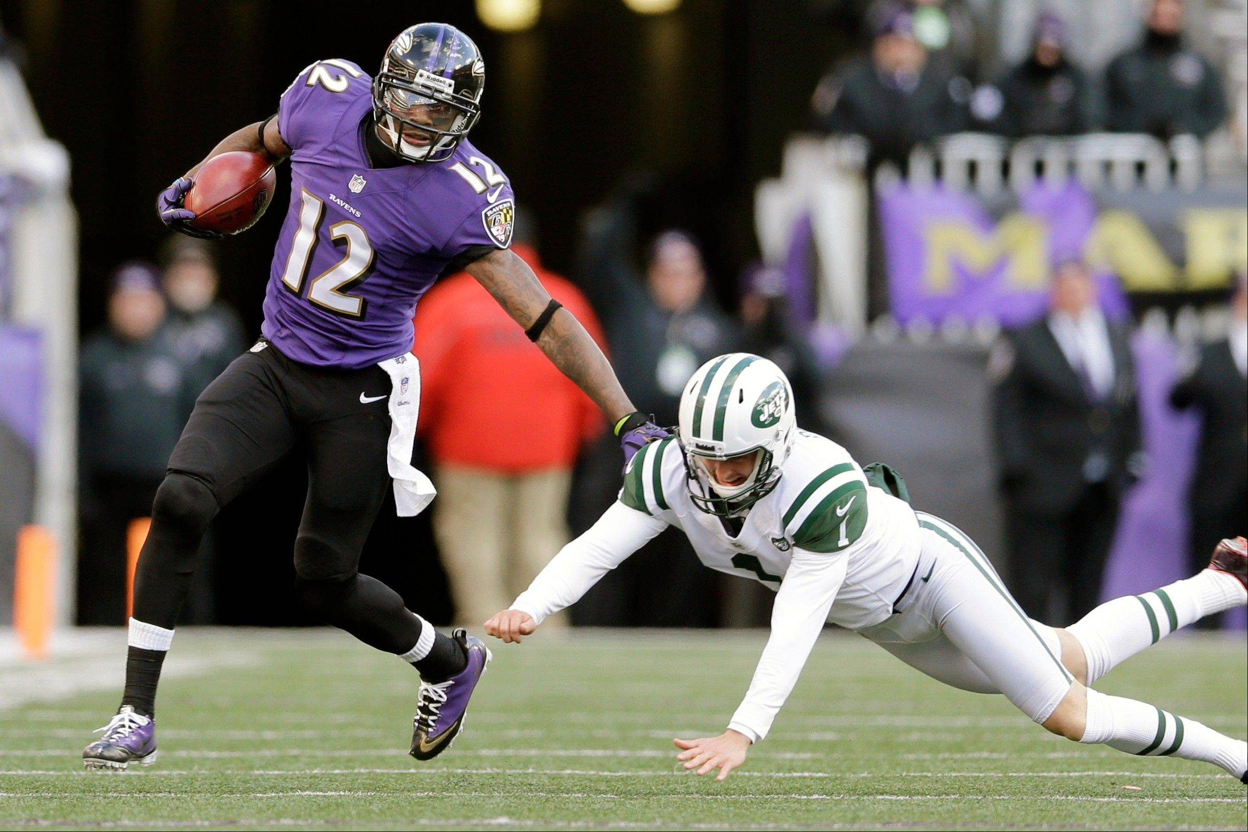 Baltimore Ravens wide receiver Jacoby Jones, left, out runs New York Jets punter Ryan Quigley on a punt return during the second half of an NFL football game in Baltimore, Sunday, Nov. 24, 2013.
