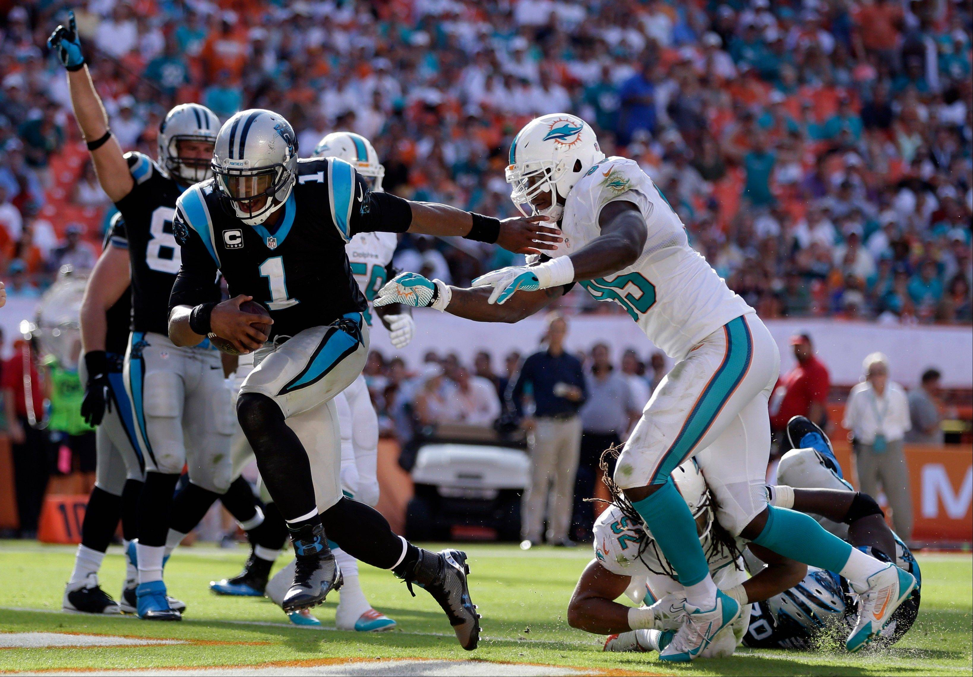Carolina Panthers quarterback Cam Newton (1) avoids a tackle by Miami Dolphins defensive end Dion Jordan (95) to score a touchdown during the second half of an NFL football game on Sunday, Nov. 24, 2013, in Miami Gardens, Fla.