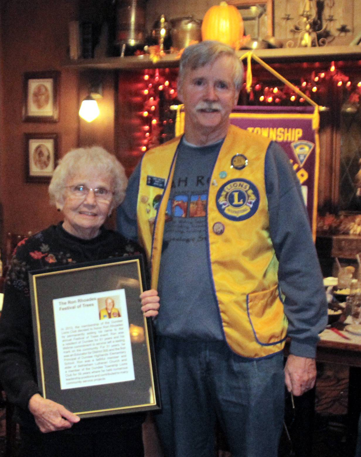 Jim McClung, Dundee Township Lions Vice President presents framed copy of sign to honor Ron Rhoades to Jeanette Rhoades, Ron's wife.