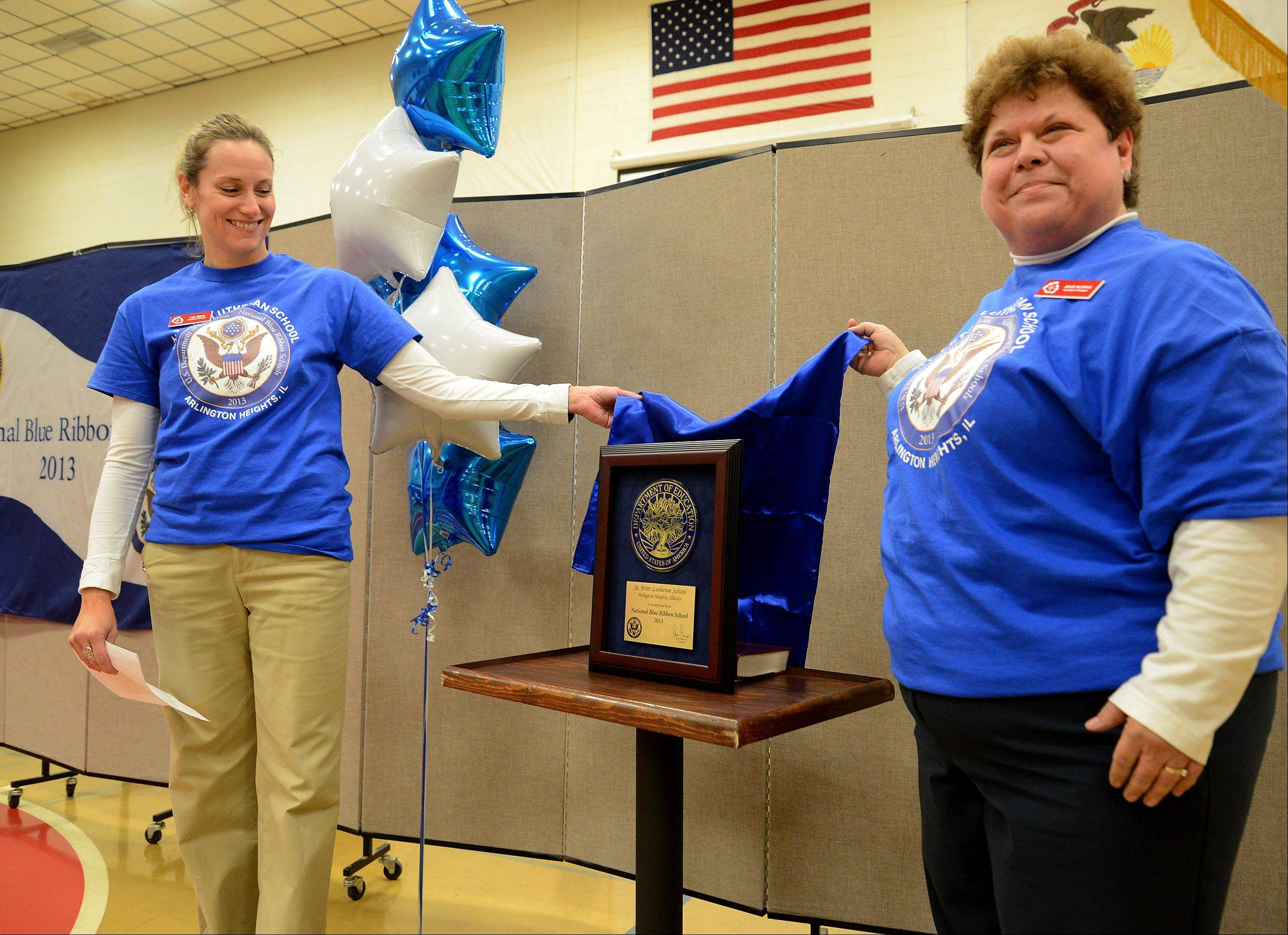 Assistant Principals Lisa Smith, left, and Julie Klopke unveil the Blue Ribbon Monday, which was awarded to St. Peter Lutheran School in Arlington Heights during an assembly.