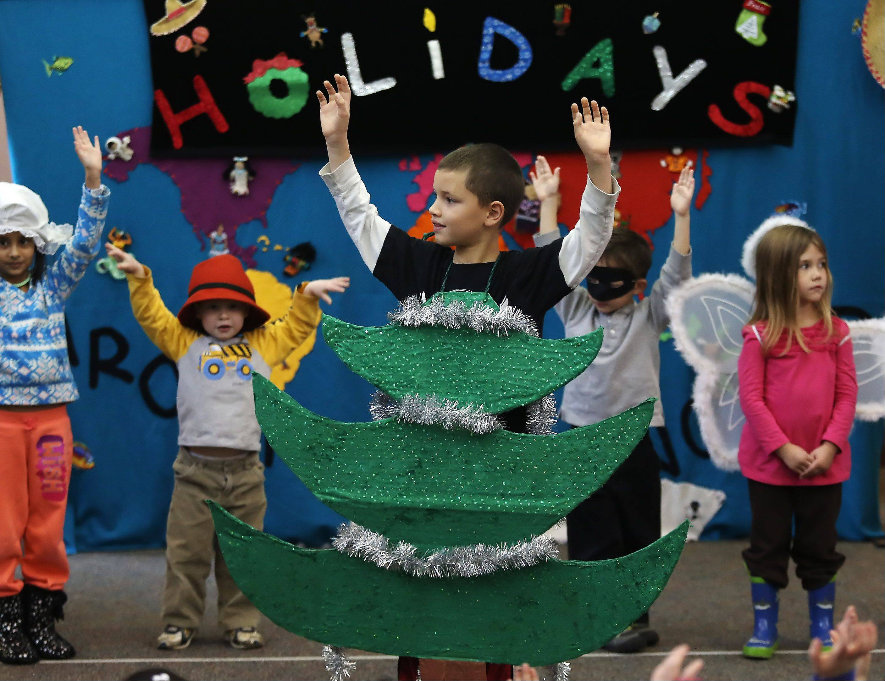 "Mason Barnett, 6, dresses as a Christmas tree as children sing ""Oh Tannenbaum"" during Monday's production of ""Holidays Around the World"" at the Lake Villa District Library. Children participated by wearing costumes, dancing and singing as they learned about holiday traditions from various countries."